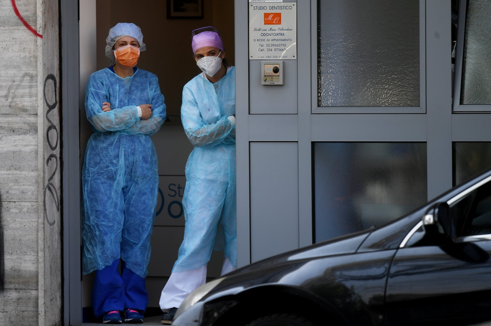 Dental staff look out of a doorway after a group who were putting red banners on memorial plaques dedicated to Italian partisans on Liberation Day following the outbreak of the coronavirus disease (COVID-19) in Milan, Italy, April 25, 2020. (Reuters Photo)