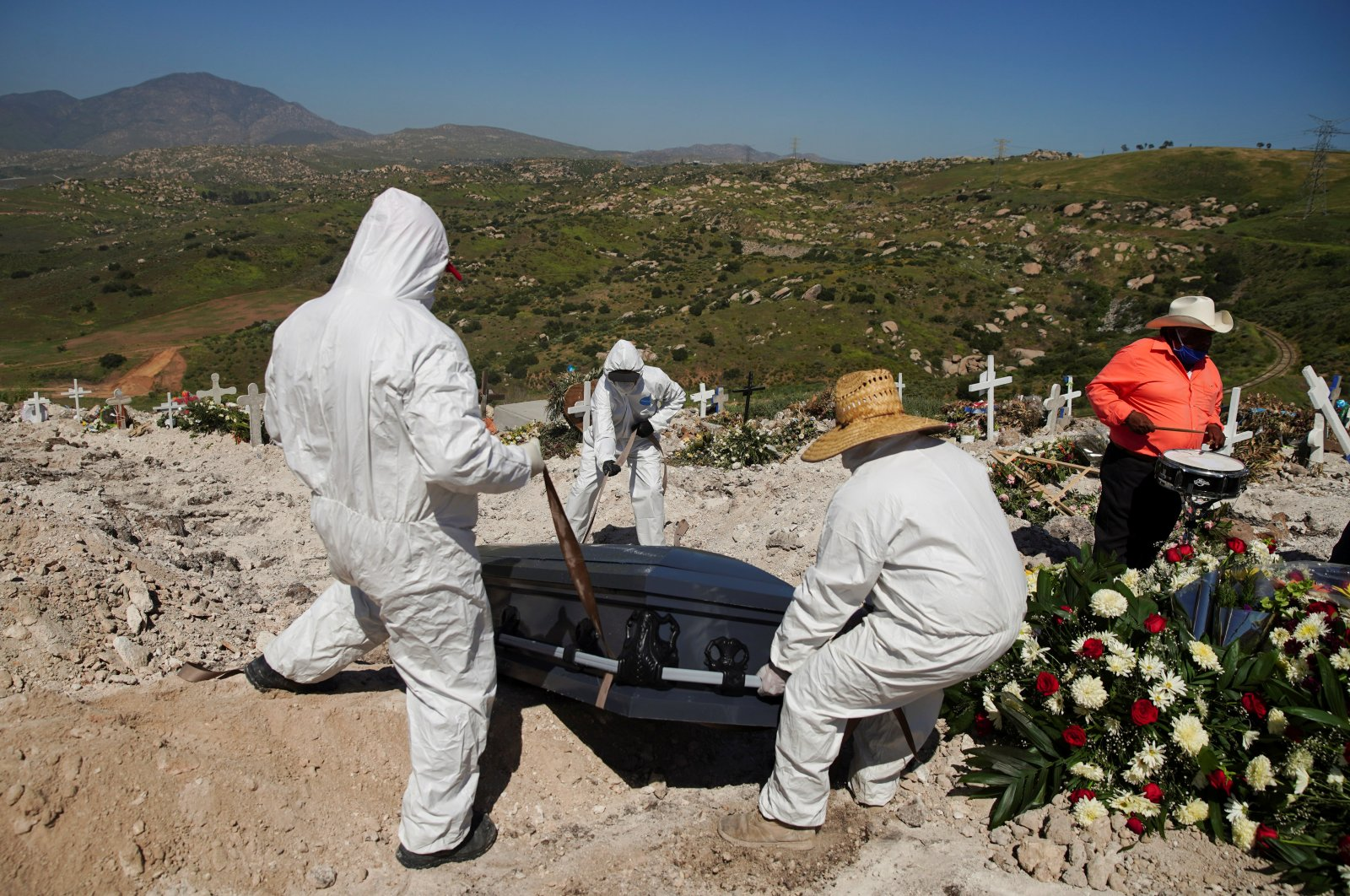 Workers in protective suits place the coffin of Jesus Osorio Flores, who died of the coronavirus disease (COVID-19), into a grave at Tijuana Municipal Cemetery No. 13, in Tijuana, Mexico April 24, 2020. (Reuters Photo)