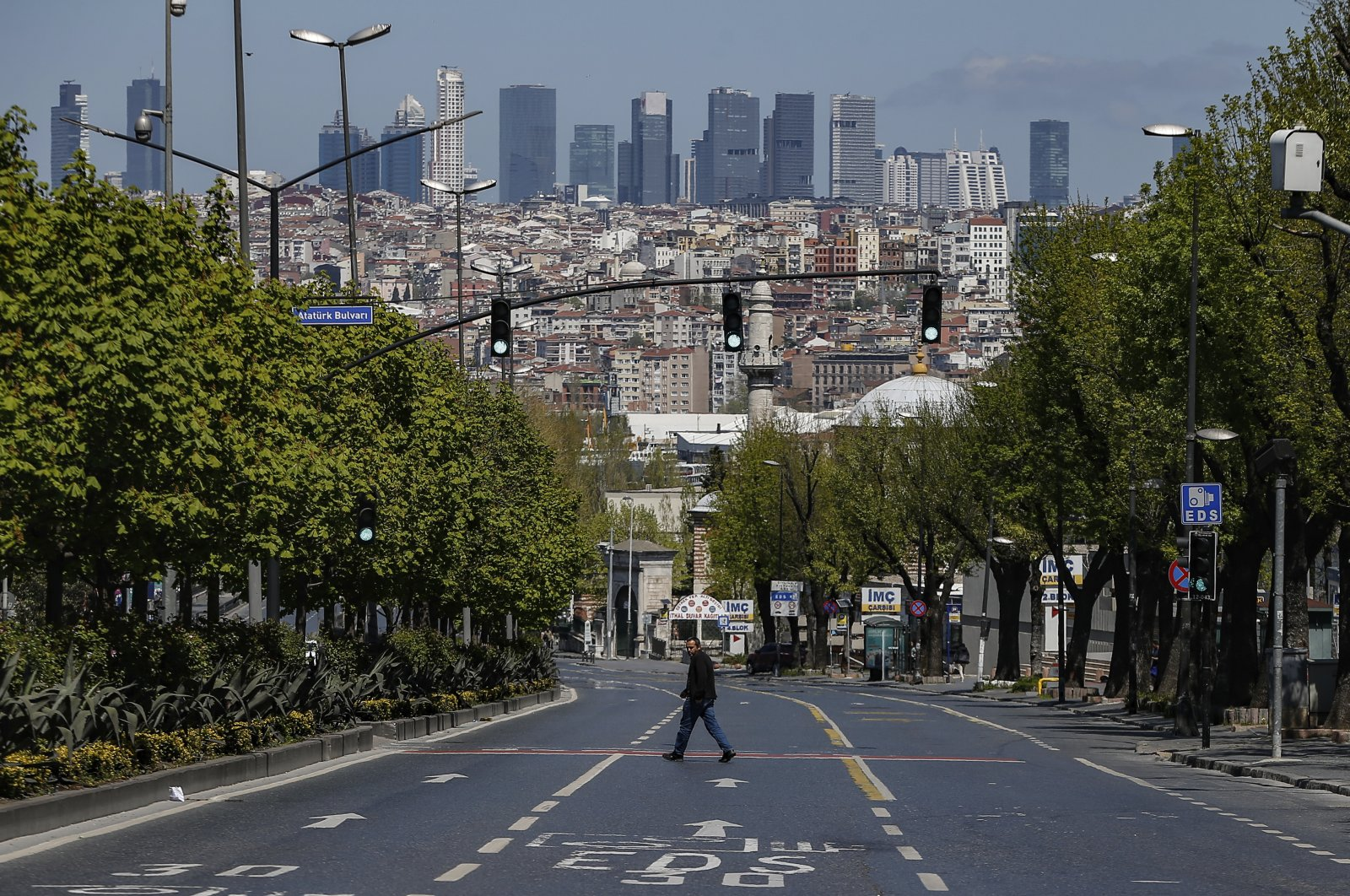 A man crosses a deserted road in Istanbul, during the first day of the holy fasting month of Ramadan, April 24, 2020. (AP Photo)