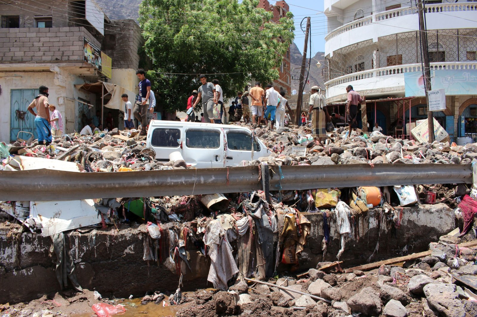 People inspect damage caused by floods on a street in Aden, Yemen, April 22, 2020. (Reuters Photo)