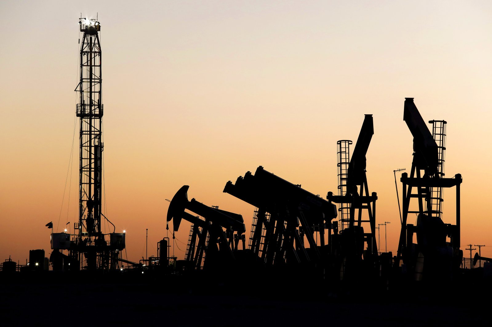 An oil rig stands at the end of a row of pump jacks shortly after sunset outside of Midland, Texas, April 24, 2020. (AP Photo)