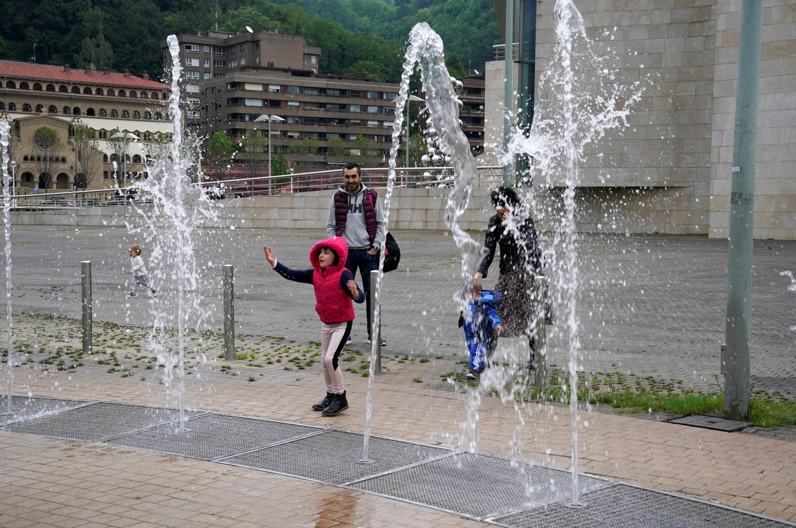 A girl plays in a fountain at the Guggenheim Museum, after restrictions were partially lifted for children, Bilbao, Spain, April 26, 2020. (REUTERS Photo)