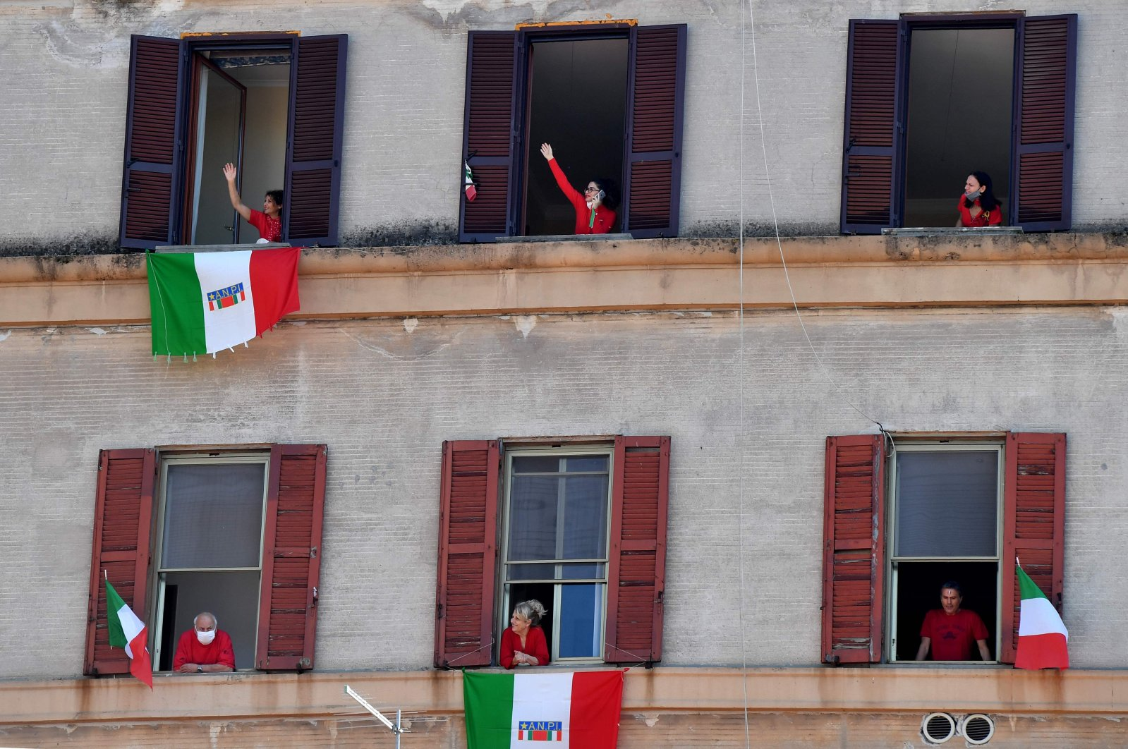 """Residents with Italian flags sing Italian partizan song """"Bella Ciao"""" in the Garbatella district of Rome, April 25, 2020. (AFP Photo)"""