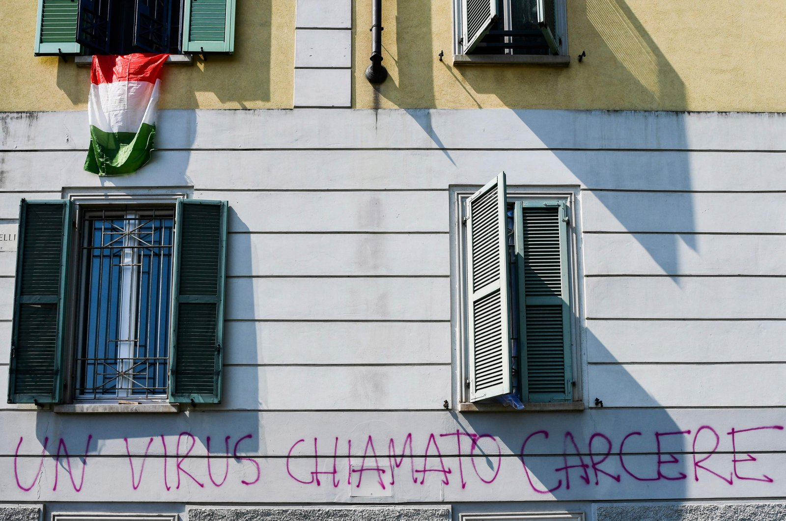"""A wall with graffiti under an Italian flag reads """"A virus called prison,"""" Milan, Italy, April 24, 2020. (AFP Photo)"""