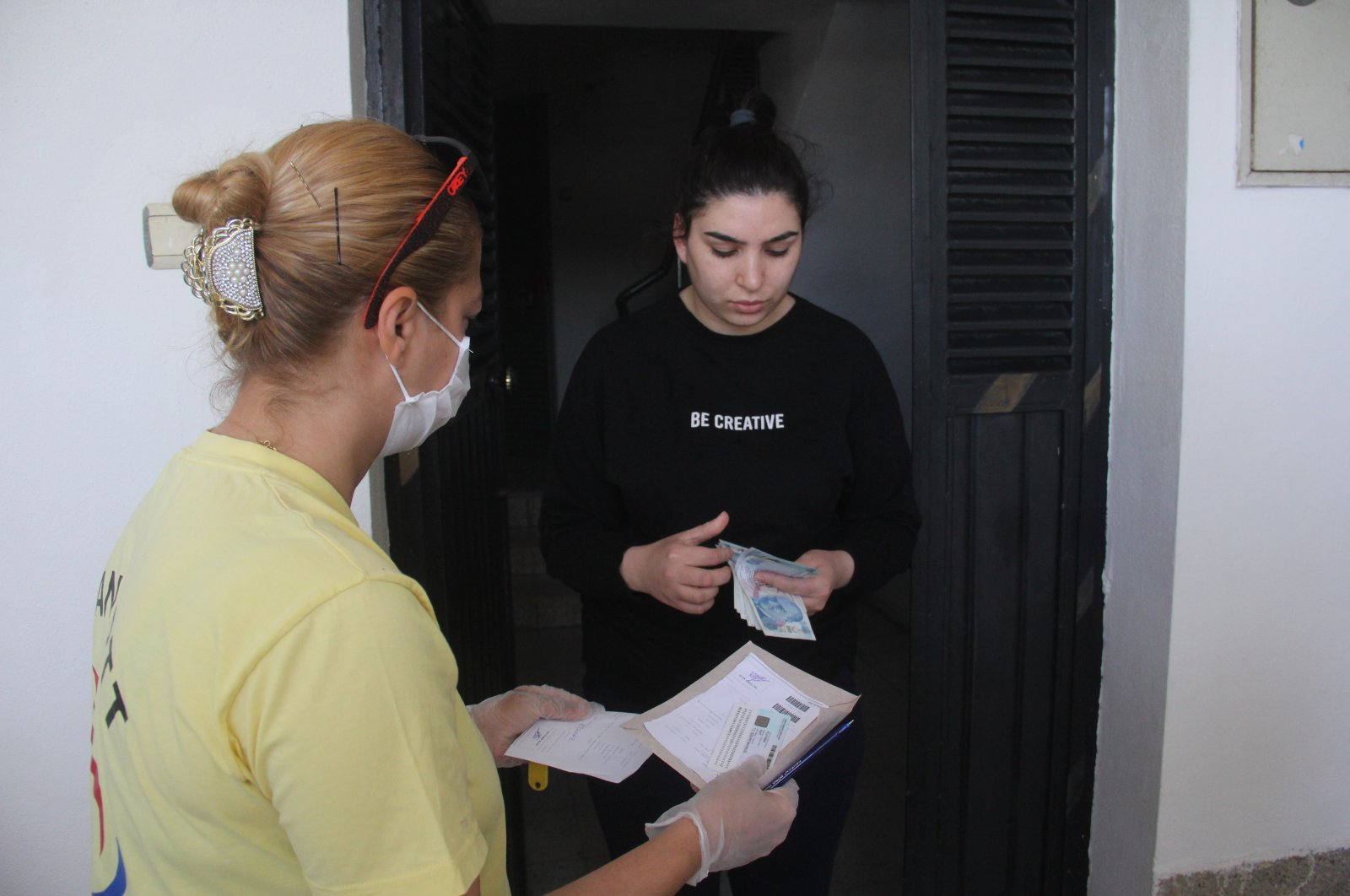 A postal worker delivers TL 1,000 cash aid to a woman in Adana, Turkey, April 21, 2020. (İHA Photo)