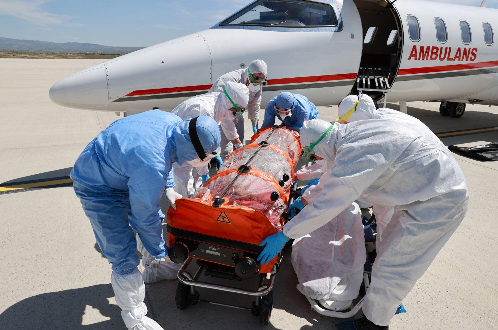Medics take Emrullah Gülüşken off an air ambulance from Sweden at Ankara Esenboğa Airport, Ankara, Turkey, April 26, 2020. (DHA Photo)
