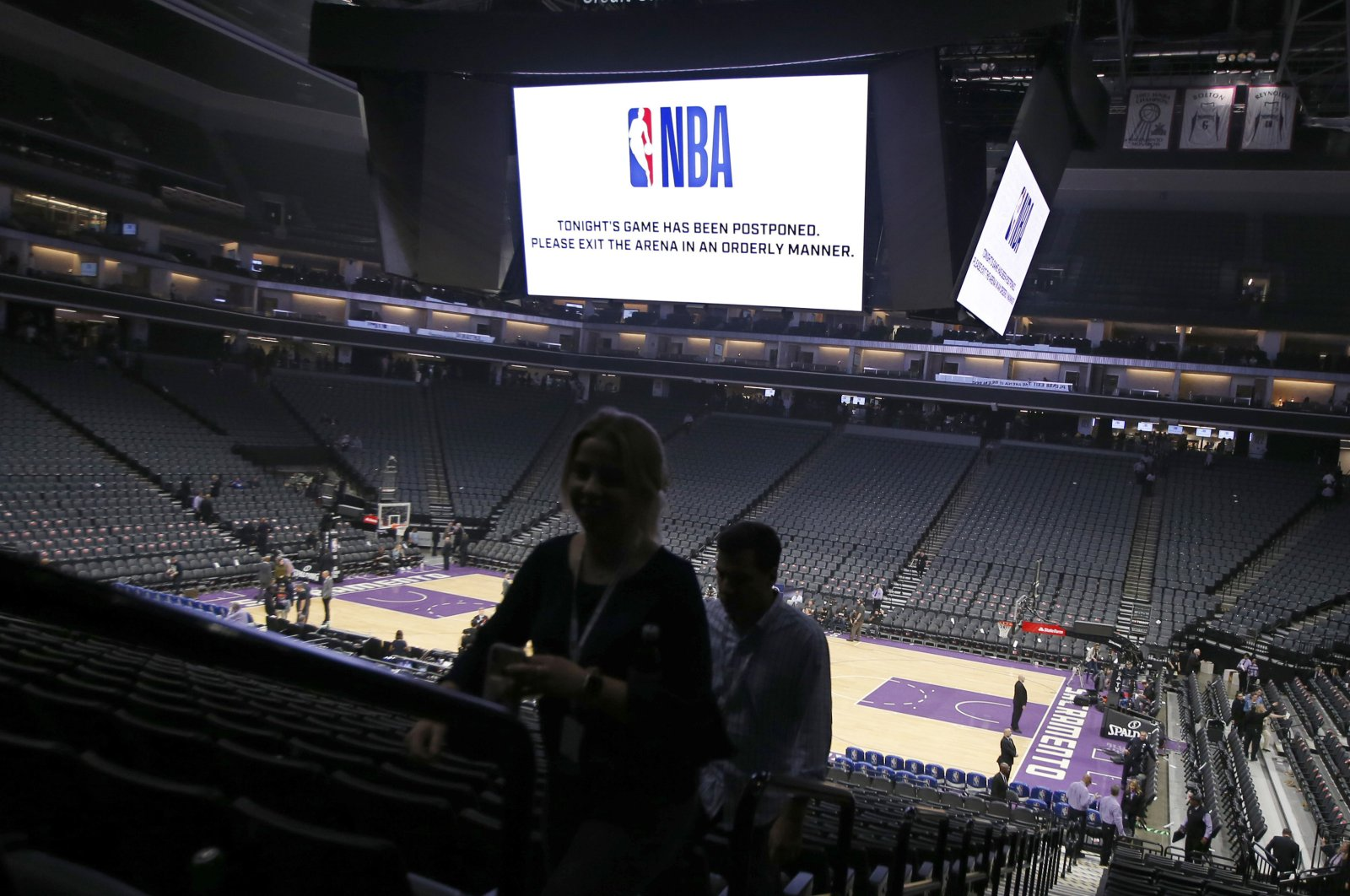 """Fans leave the Golden 1 Center in Sacramento, Calif. after the NBA basketball game between the New Orleans Pelicans and Sacramento Kings was postponed at the last minute over an """"abundance of caution"""" after a player for the Jazz tested positive for the coronavirus, March 11, 2020 photo. (AP Photo)"""