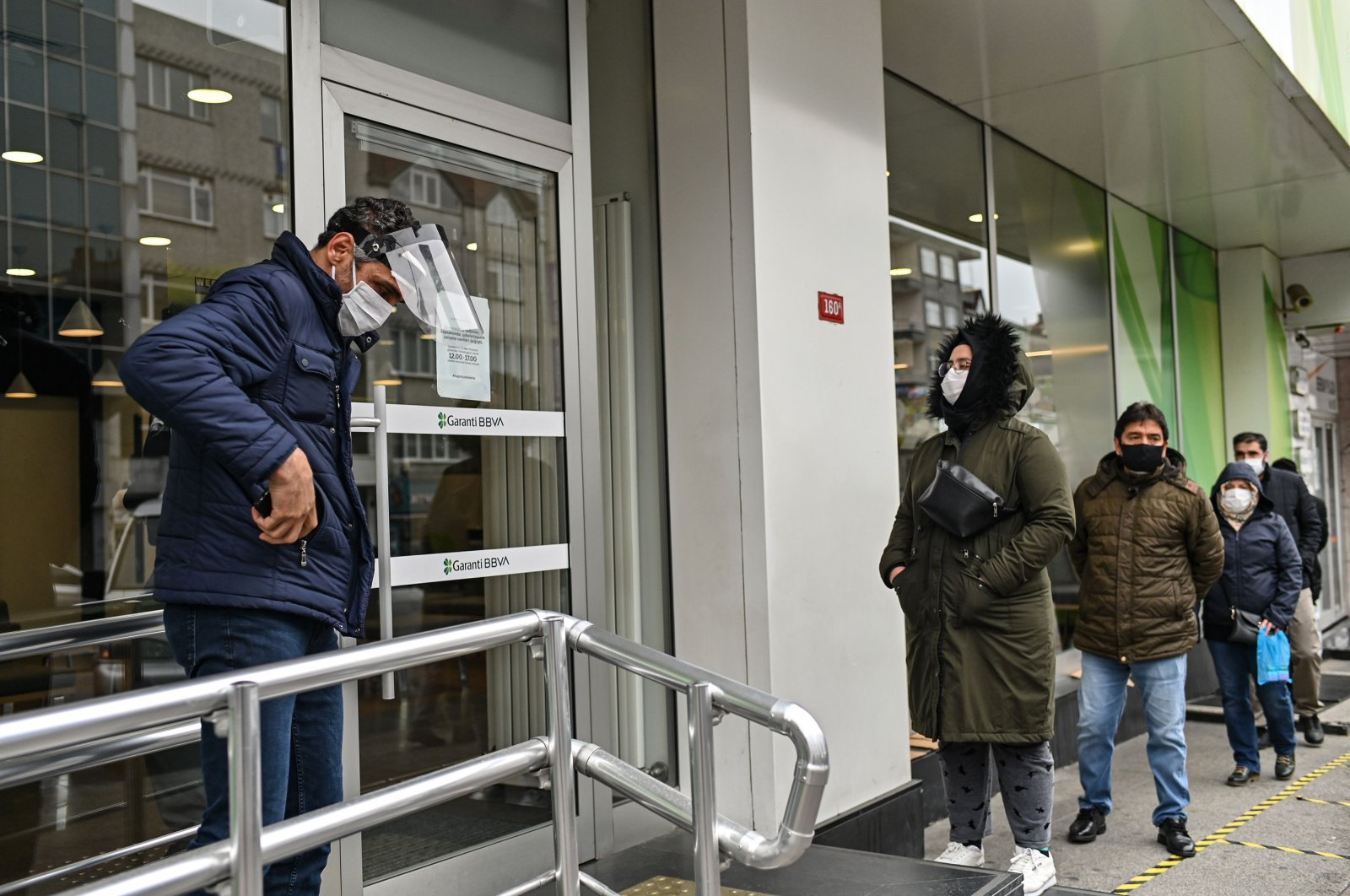 People queue observing social distancing outside a bank in Gaziosmanpaşa in Istanbul, Turkey, April 21, 2020, amid the COVID-19 pandemic. (AFP Photo)