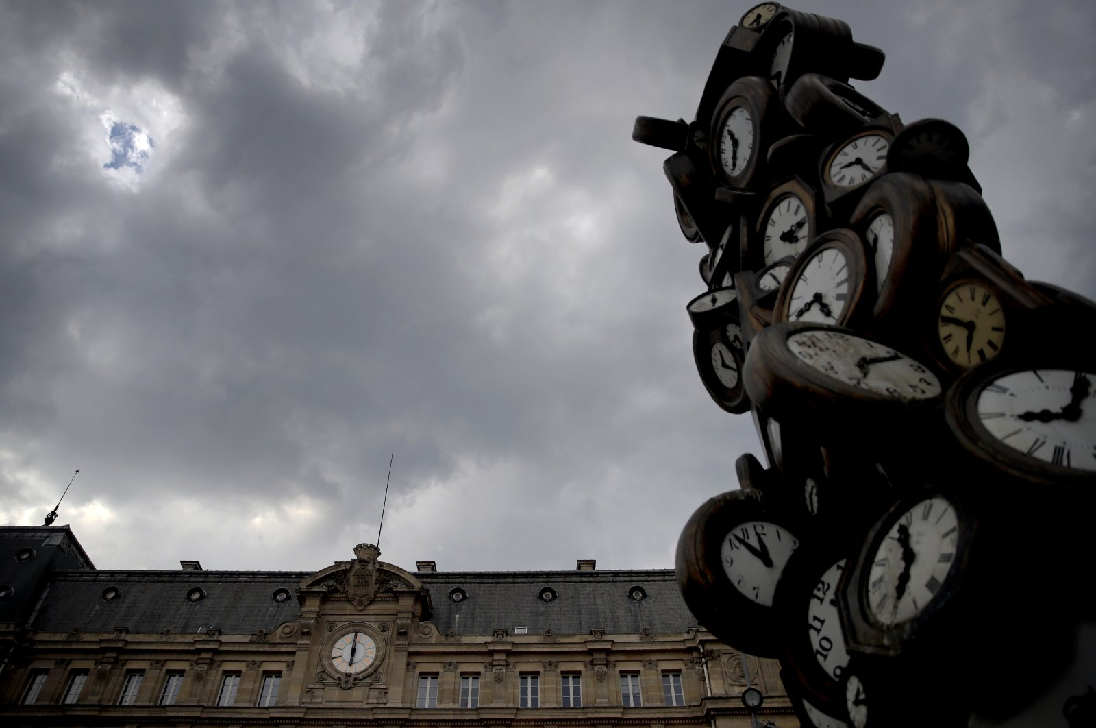 "The Saint Lazare train station clock (L) and the sculpture named ""L'Heure de Tous"" (""Everyone's Time"") by French artist Arman is photographed in Paris, France, April 24, 2020. (AP Photo)"