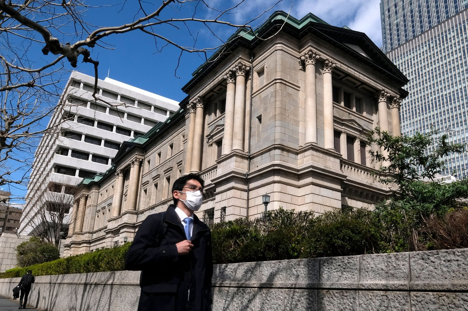 A pedestrian wearing a face mask walks in front of the Bank of Japan headquarters in Tokyo, March 16, 2020. (AFP Photo)