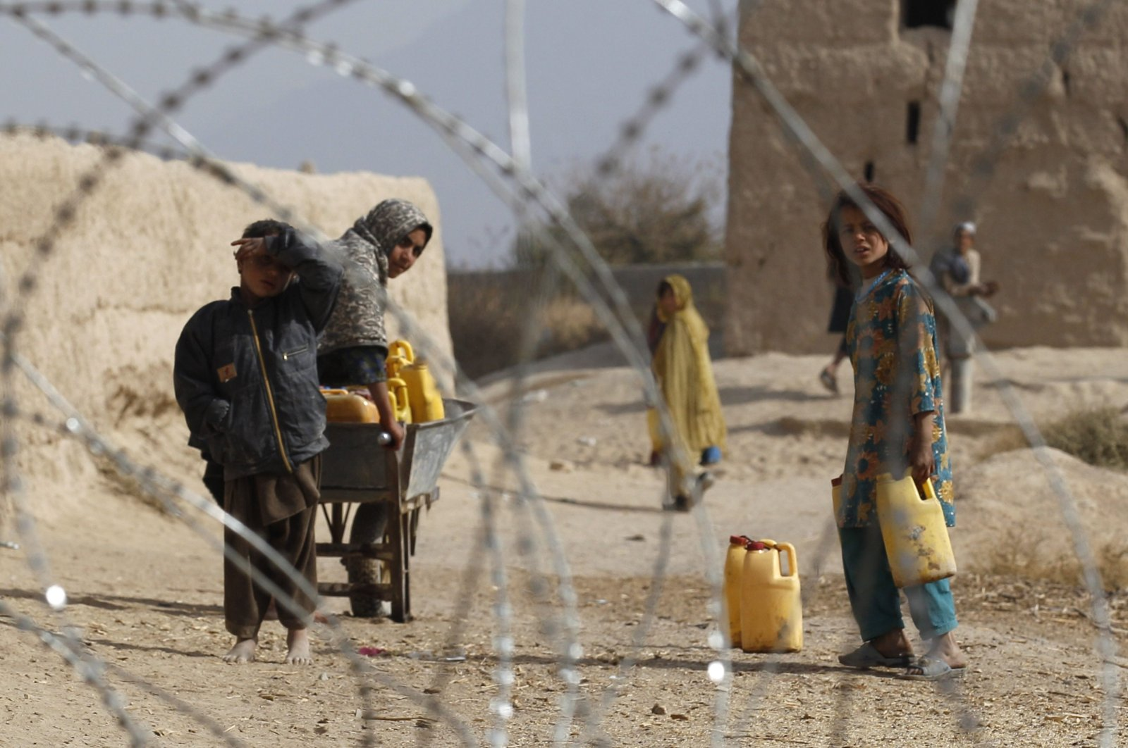 Afghan children look from behind a razor wire at an outpost in Zhari district in Kandahar Province, Nov. 20, 2010. (REUTERS Photo)