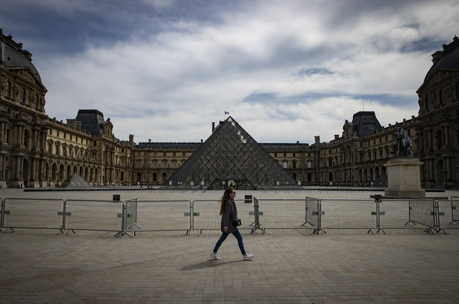 A woman walks past the deserted Louvre in Paris, France, 21 April 2020. France is under lockdown in an attempt to stop the widespread of the SARS-CoV-2 coronavirus causing the Covid-19 disease. (EPA Photo)
