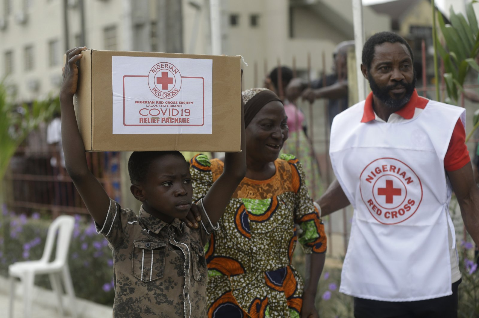 A child with his mother, from Makoko Slum, carries their food parcel distributed by the Nigerian Red Cross, provided for those under coronavirus-related movement restrictions, in Lagos, Nigeria, April 25, 2020. (AP Photo)