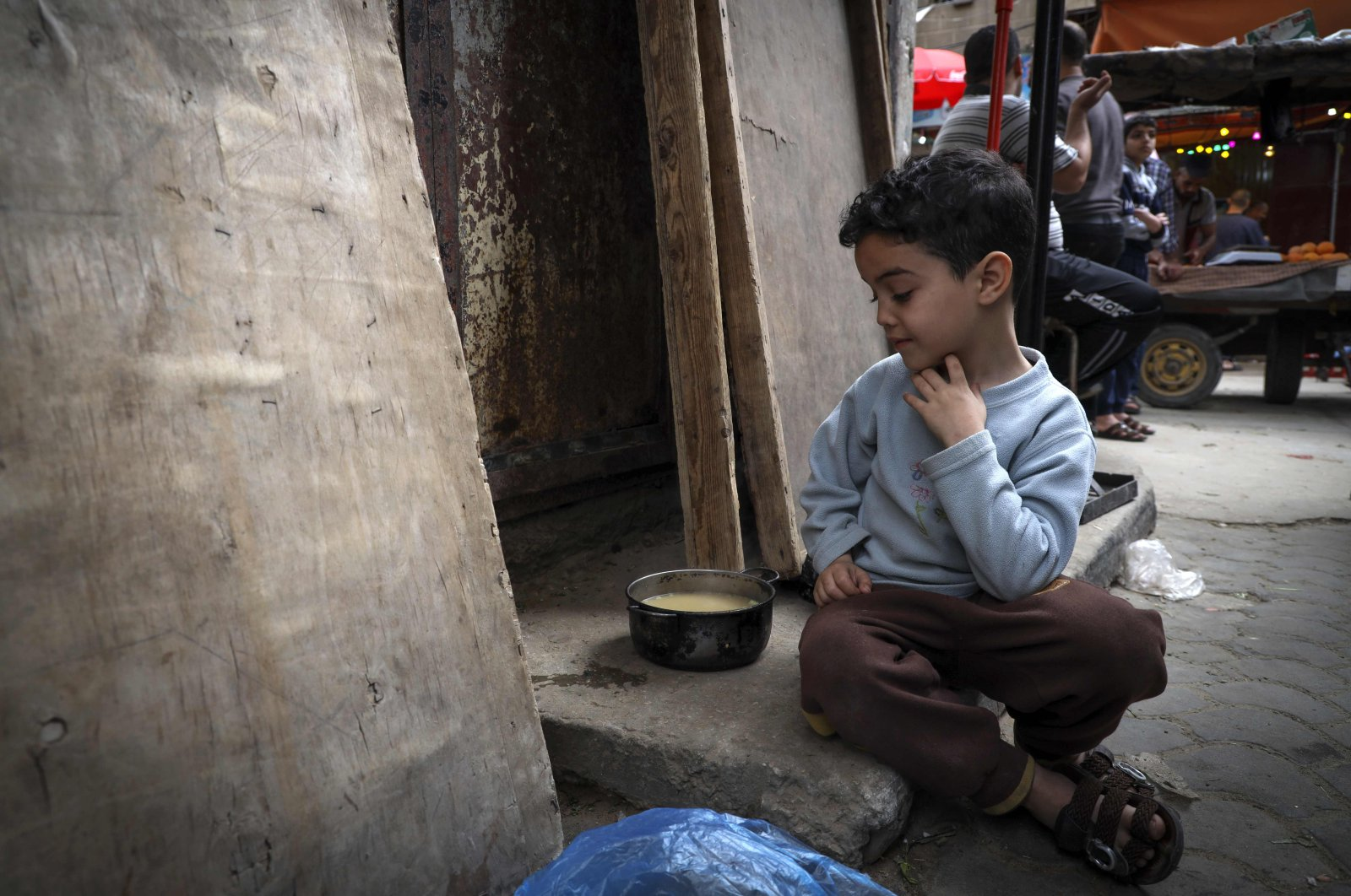 A Palestinian boy looks at his portion of soup, given out to poor families during the holy month of Ramadan, Gaza City, Palestine, April 24, 2020. (AFP Photo)