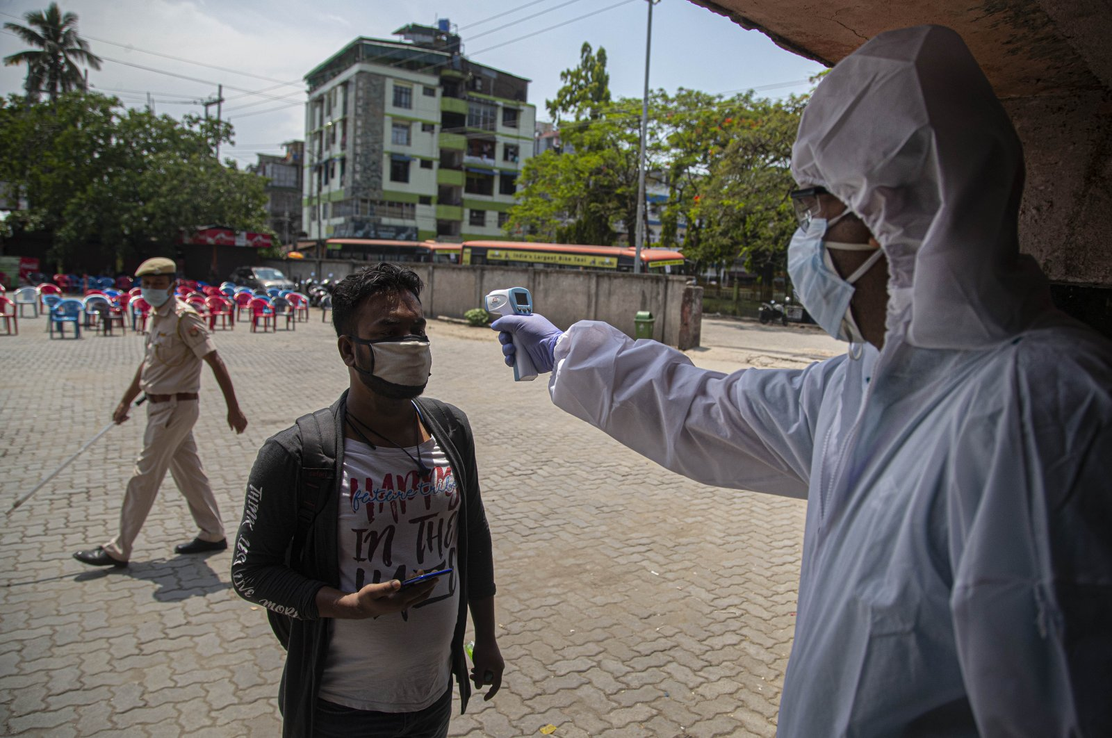 A health worker checks temperature of a passenger as people who were stranded in the city due to the month-long lockdown to curb the spread of new coronavirus, arrive to board special buses to their villages in Gauhati, India, April 27, 2020. (AP Photo)