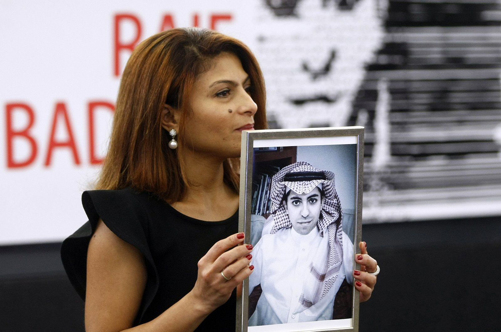 Ensaf Haidar, wife of the jailed Saudi Arabian blogger Raif Badawi, shows a portrait of her husband as he is awarded the Sakharov Prize, in Strasbourg, France, Dec. 16, 2015. (AP Photo)