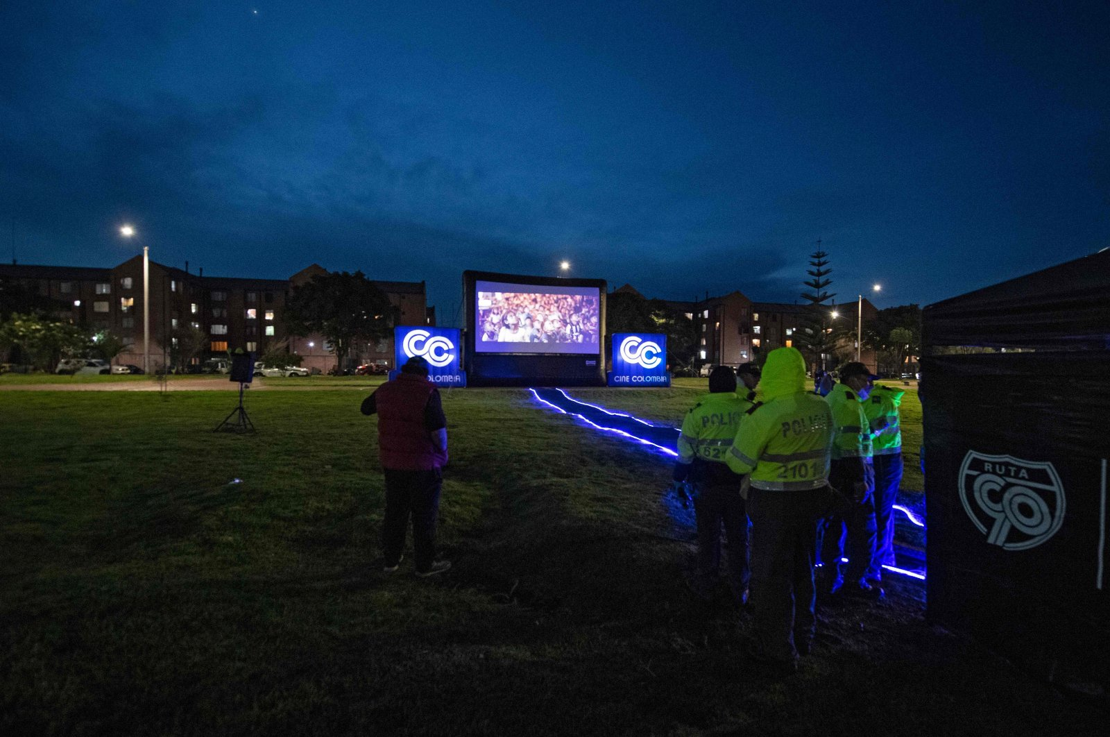 Police officers look at a film projected on a giant screen at a park so that residents under lockdown can watch from their apartments, amid the coronavirus pandemic, in Bogota, Colombia, April 23, 2020. (AFP Photo)