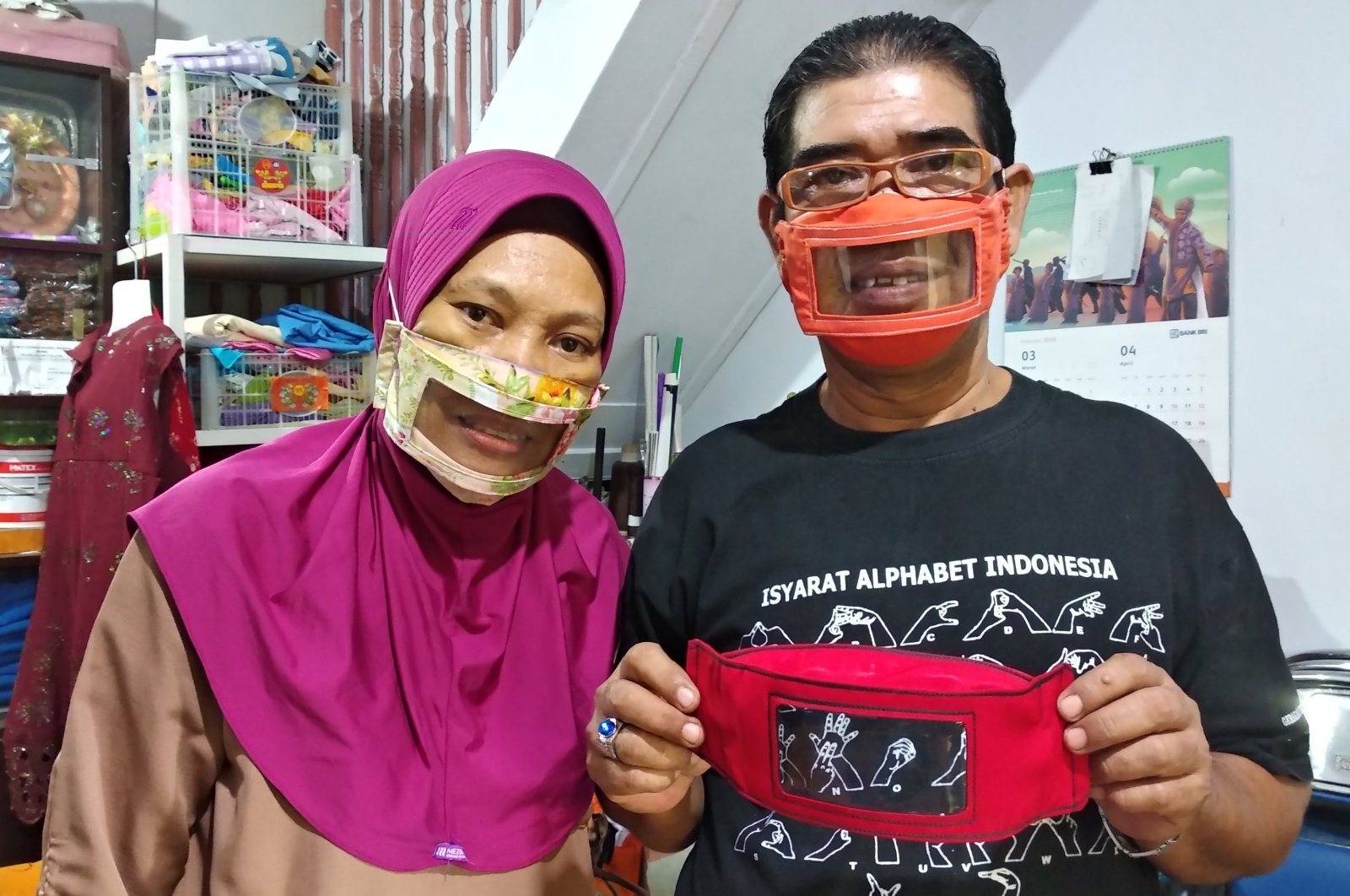 Imama Saroso (R) and his wife Faizah Badaruddin (L), who are hearing and speech-impaired, pose with homemade face masks which enable people with disabilities like them to read lips when communicating, in Makassar, South Sulawesi, April 28, 2020. (AFP Photo)