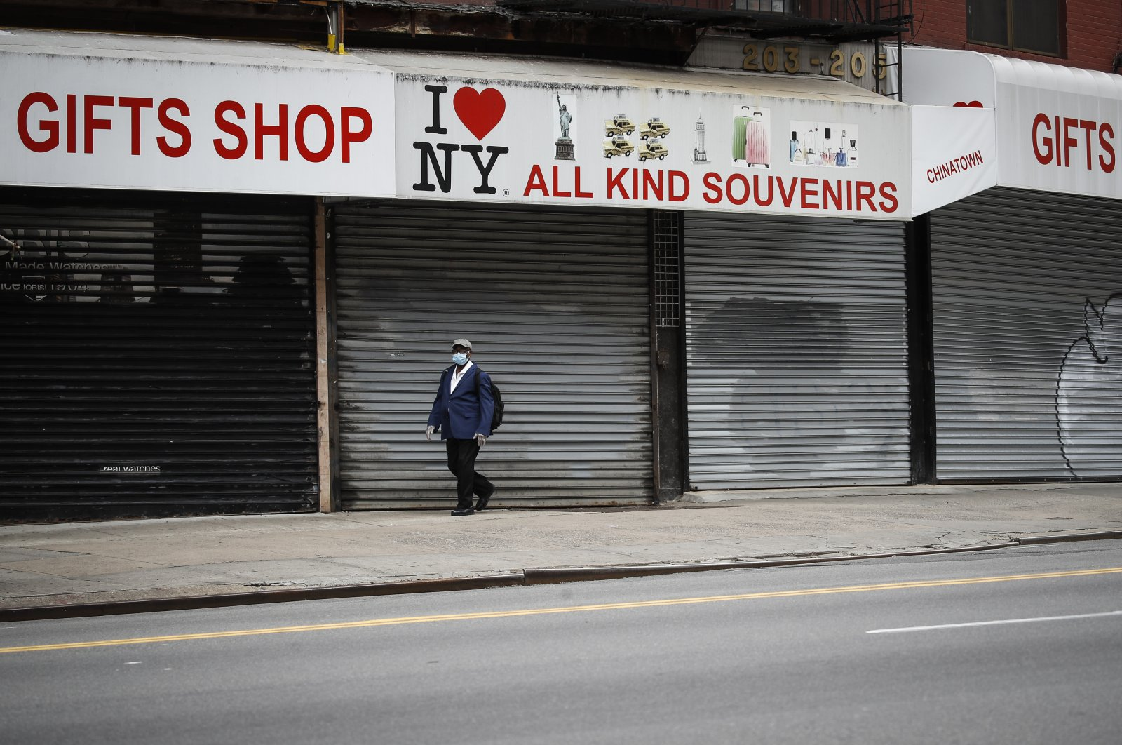 A pedestrian wearing a protective mask walks along shuttered storefronts on Canal Street during the coronavirus outbreak, New York, April 27, 2020. (AP Photo)
