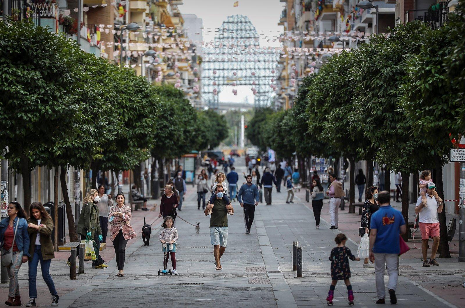 People walk down Callo San Jacinto, in Sevilla, Spain, April 26, 2020. (EPA Photo)