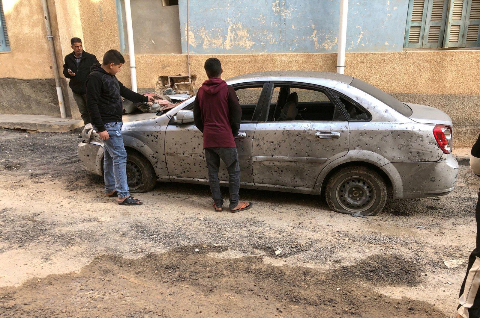 Libyan boys check a damaged car after a shell fell on a residential area of Hadba al-Badri district, in Tripoli, Libya, Jan. 28, 2020. (Reuters Photo)