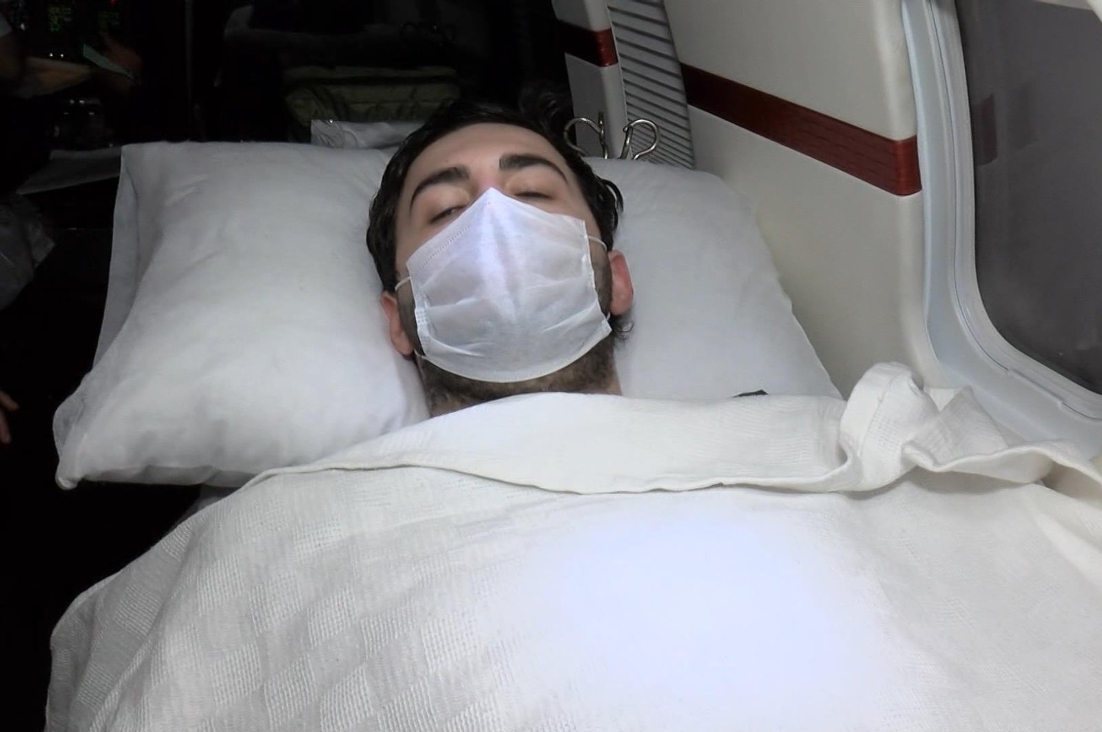 Haluk Hasan Seyithanoğlu, 24, lies on a bed inside the plane provided by the Turkish Health Ministry to take the student back to Turkey, April 27, 2020. (DHA Photo)