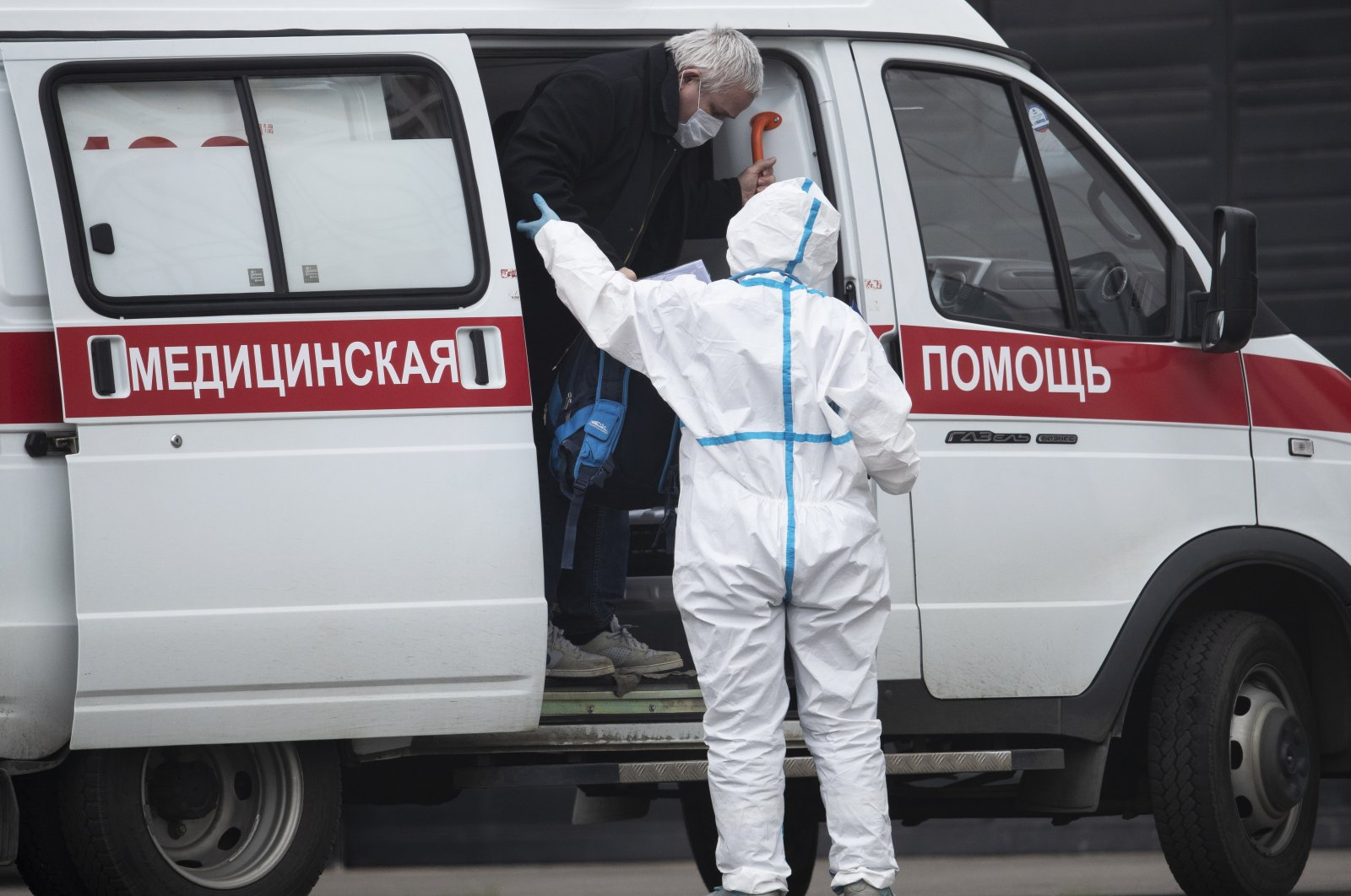 In this April 27, 2020, photo, a medical worker wearing protective gear helps a man, suspected of having the coronavirus infection, to get out from an ambulance at a hospital in Kommunarka, outside Moscow, Russia. (AP Photo)