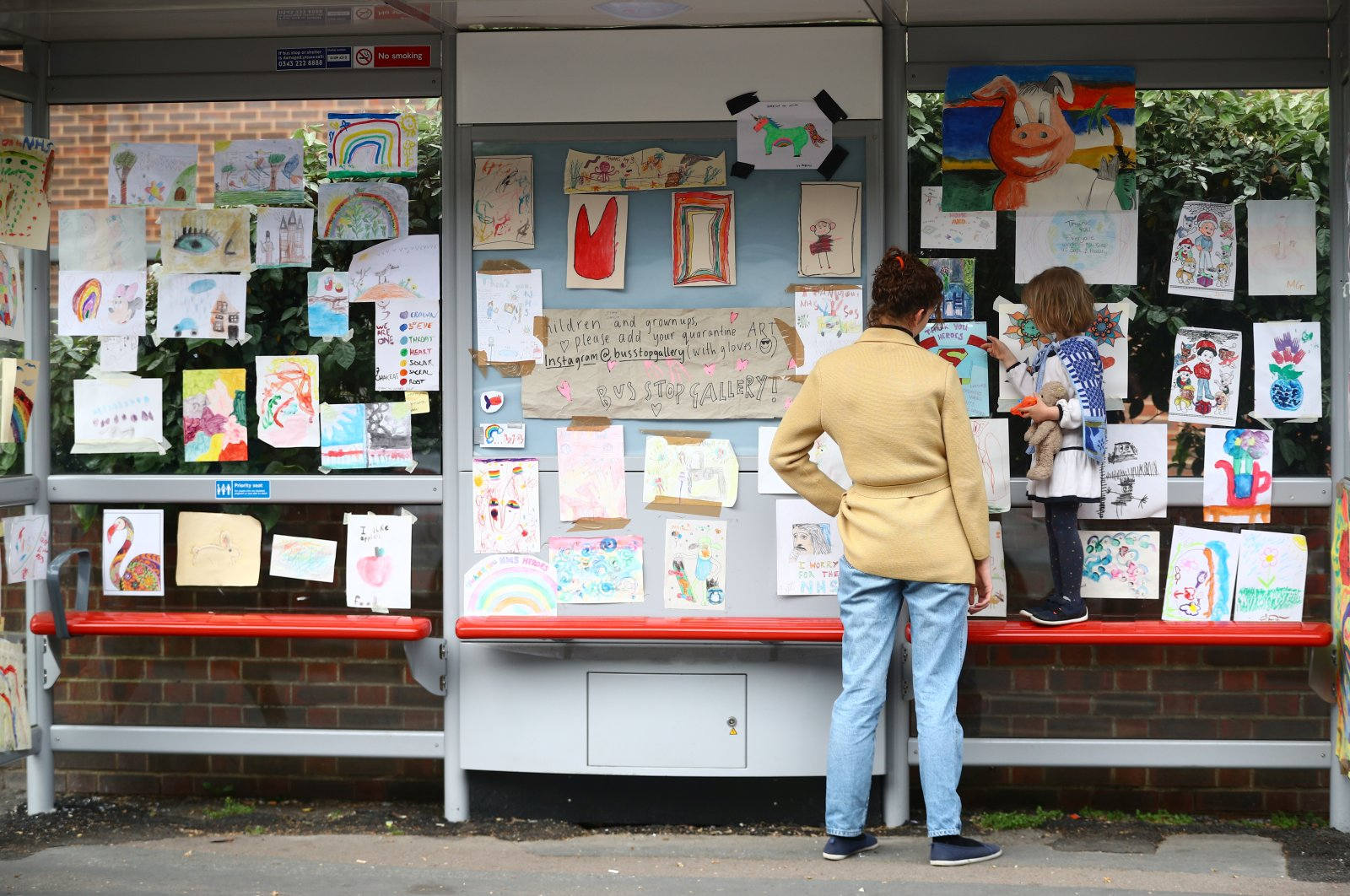"Sarah Lamarr and her 4-year-old daughter, Rosie, who started a ""bus stop gallery"" look at artwork at the bus stop following the outbreak of the coronavirus, London, Britain, April 27, 2020. (Reuters Photo)"