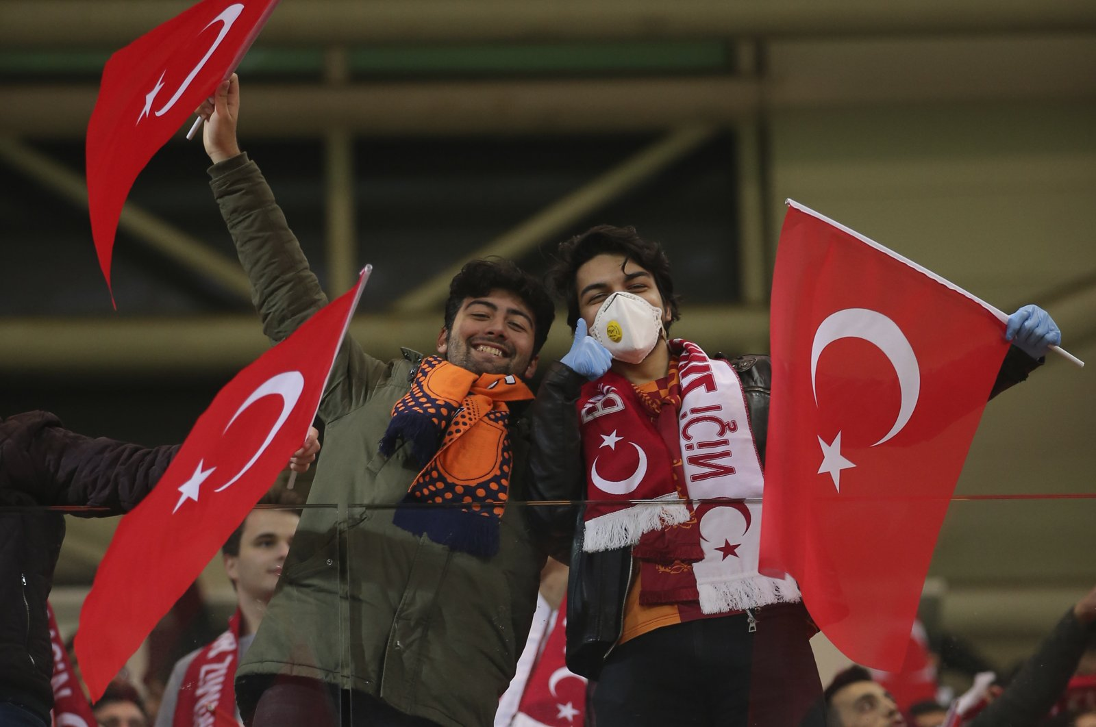 Spectators, some wearing masks because of the coronavirus outbreak, wave Turkish flags prior to the first leg of a Europa League top 16 soccer match between Başakşehir and Copenhagen, in Istanbul, March 12, 2020. (AP Photo)
