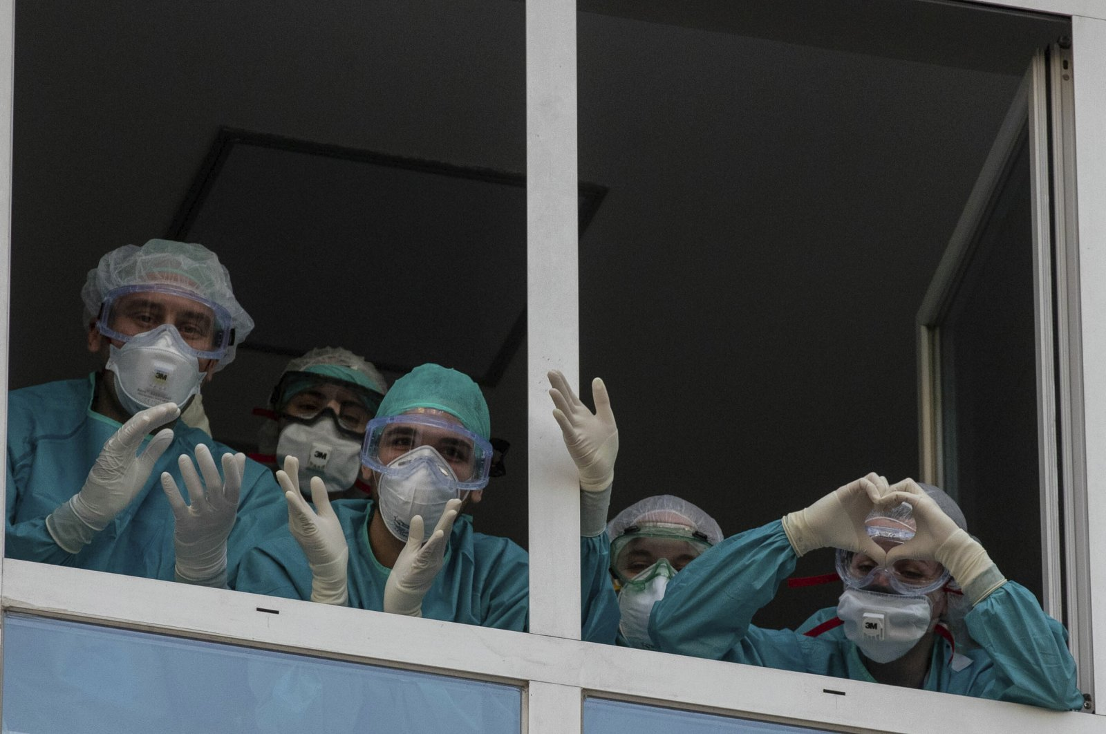Health workers react as people applaud from their nearby houses in support of the medical staff, Madrid, April 15, 2020. (AP Photo)
