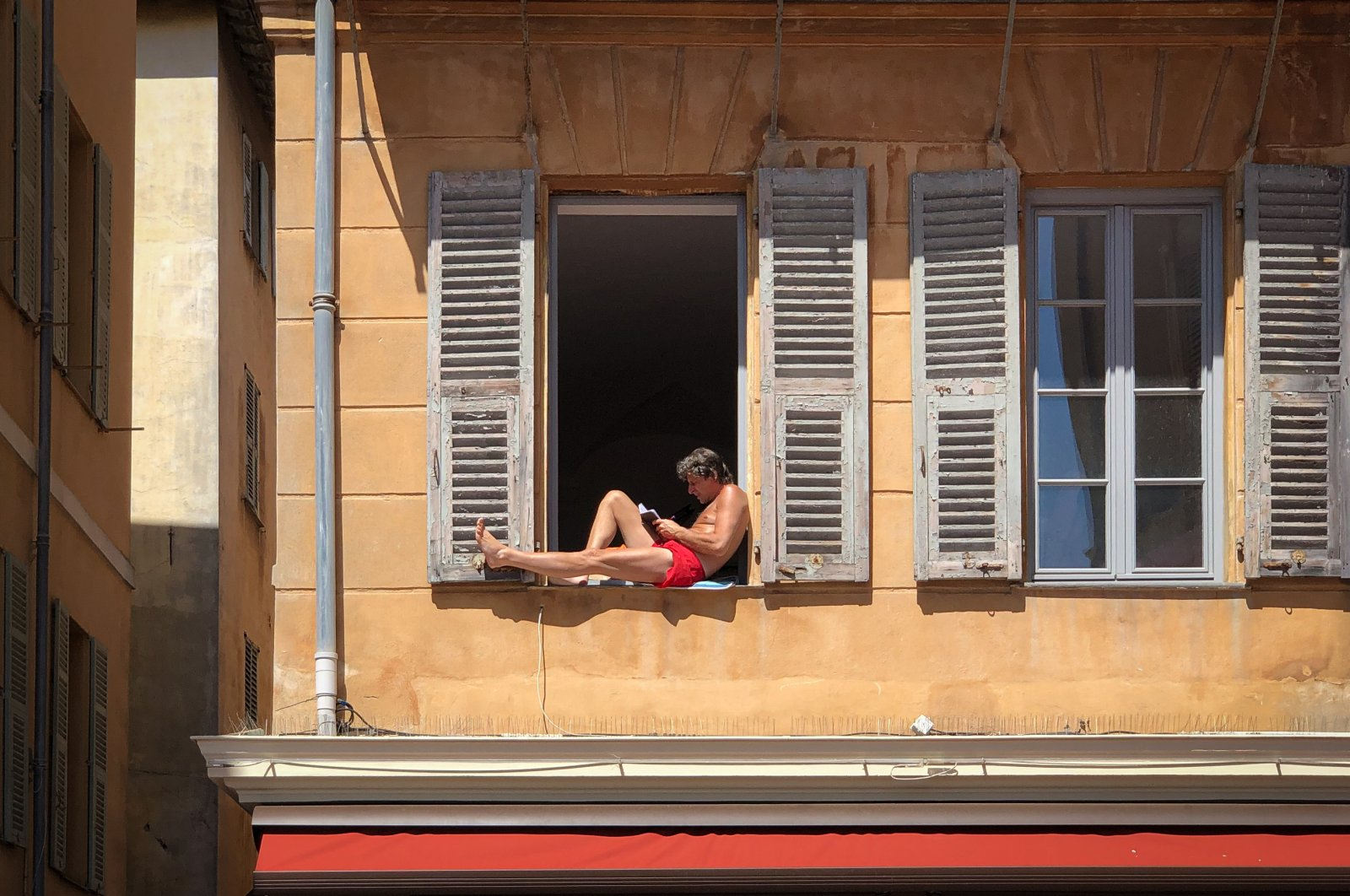 A man alone and confined to his apartment, sunbathing shirtless while reading a book in his window, in old Nice. (Reuters Photo)