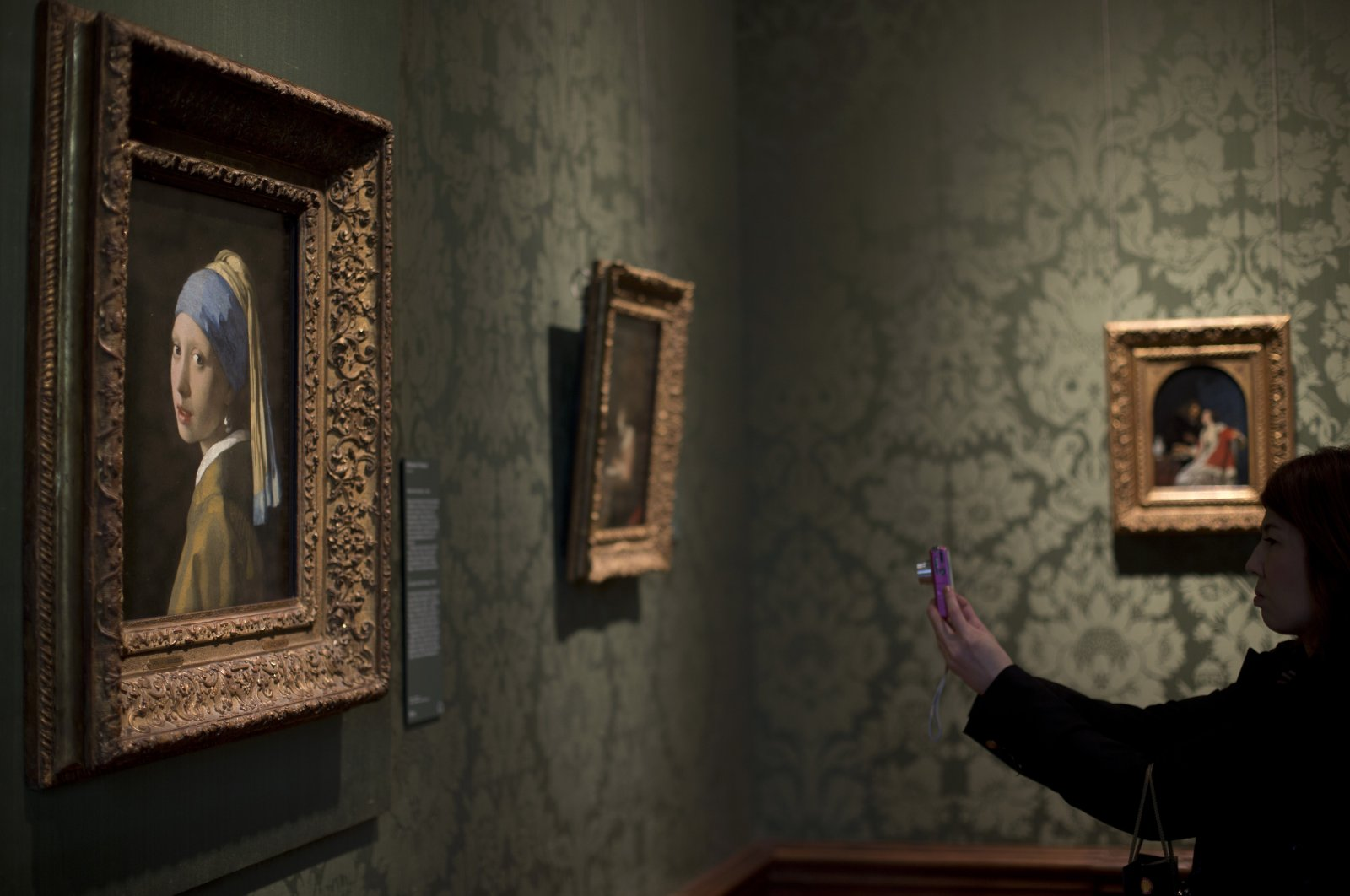 """A visitor takes a picture of Johannes Vermeer's 17th century masterpiece """"Girl with a Pearl Earring,"""" (L) during a preview for the press of the renovated Mauritshuis in The Hague, the Netherlands, June 20, 2014. (AP Photo)"""