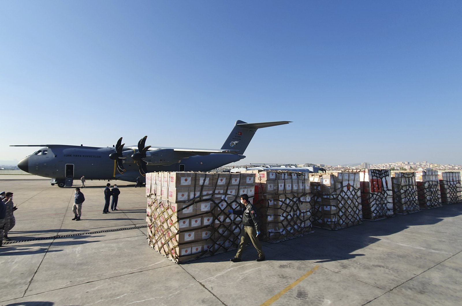 In this handout photo provided by the Turkish Defense Ministry, Turkish soldiers prepare to load a military cargo plane with Personal Protection Equipment donated by Turkey to help United States combat the new coronavirus outbreak, at the Etimesgut airport outside Ankara, Turkey, Tuesday, April 28, 2020. (AP Photo)