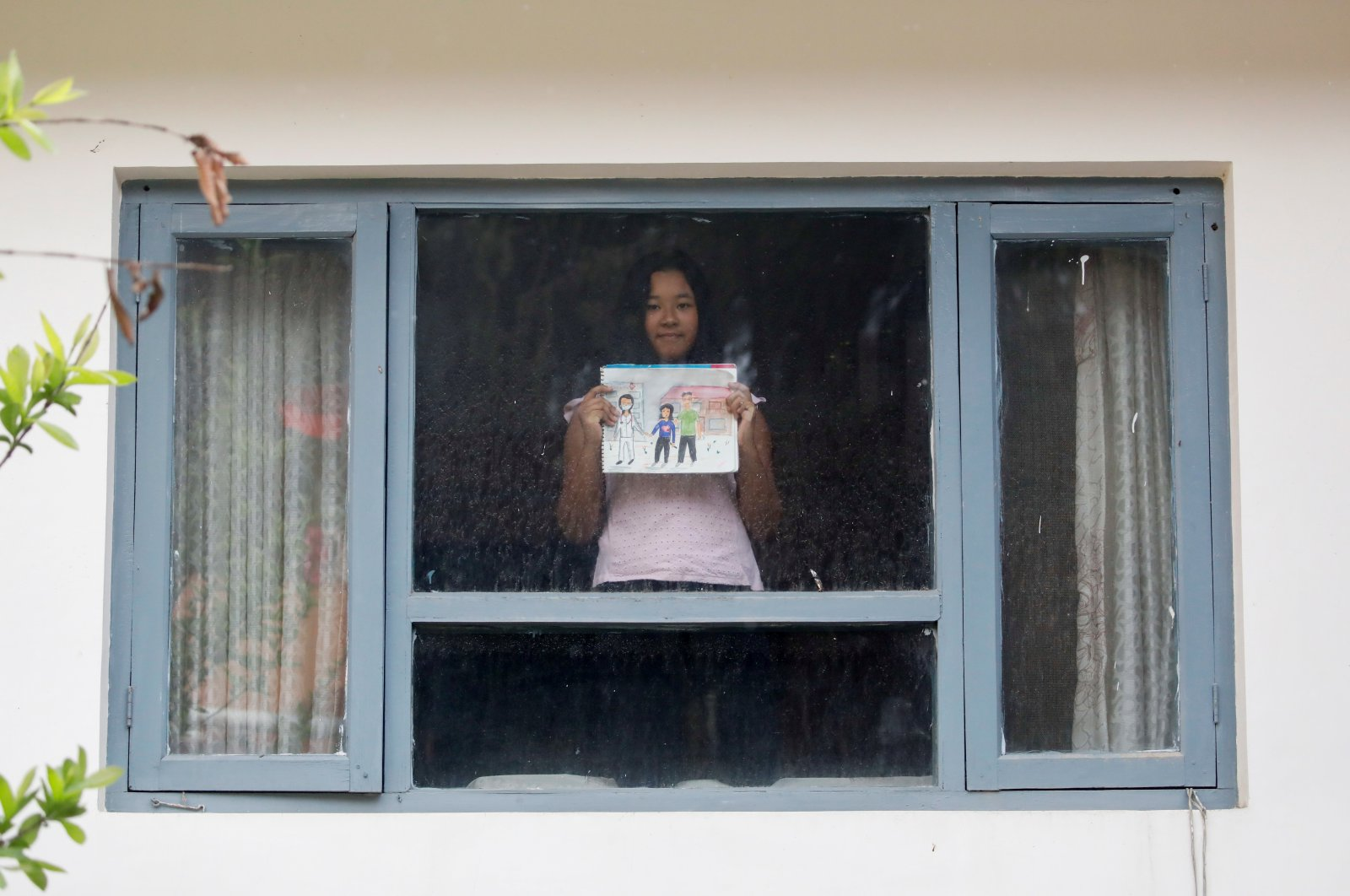 A girl poses for a photograph while holding a picture that she drew during the coronavirus outbreak, Kathmandu, Nepal, April 16, 2020. (REUTERS Photo)