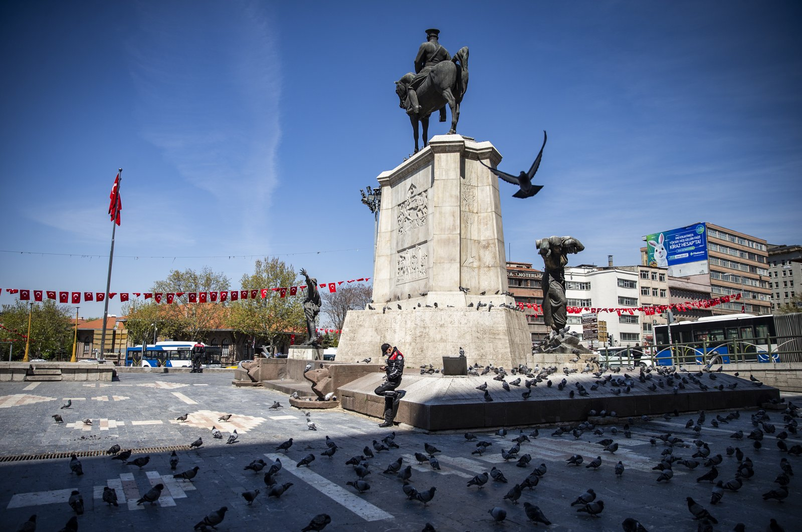 A police officer stands next to a statue at otherwise busy Ulus Square, in Ankara, Turkey, April 28, 2020. (AA Photo)