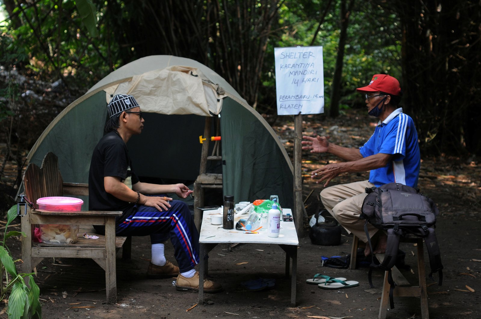 Abdullah Al Mabrur talks with his neighbour outside a tent he used for self-quarantine on a river bank after he came back from Pekanbaru, to prevent the spread of the coronavirus disease in Klaten, Central Java province, Indonesia, April 20, 2020. (Reuters Photo)