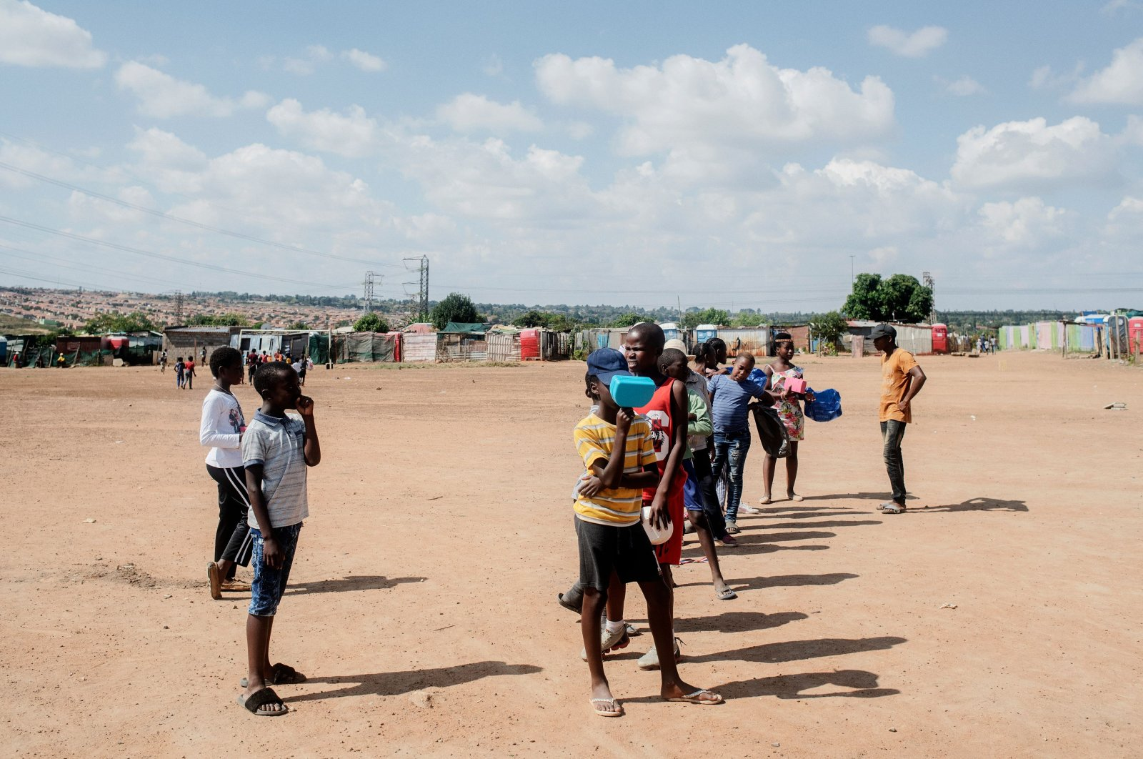 Children queue while they wait for the daily food distribution in the Tembisa informal settlement, Johannesburg on April 24, 2020. (AFP Photo)