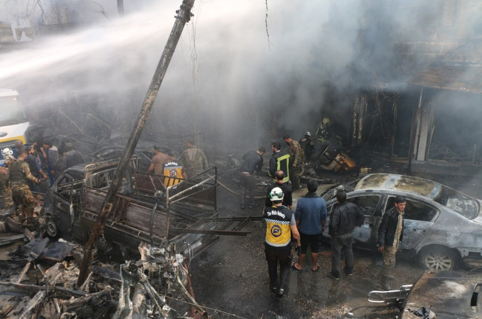 Civil rescue workers work among the burned cars and rubble following the YPG/PKK terrorist attack in Afrin, northwestern Syria, April 28, 2020. (IHA Photo)