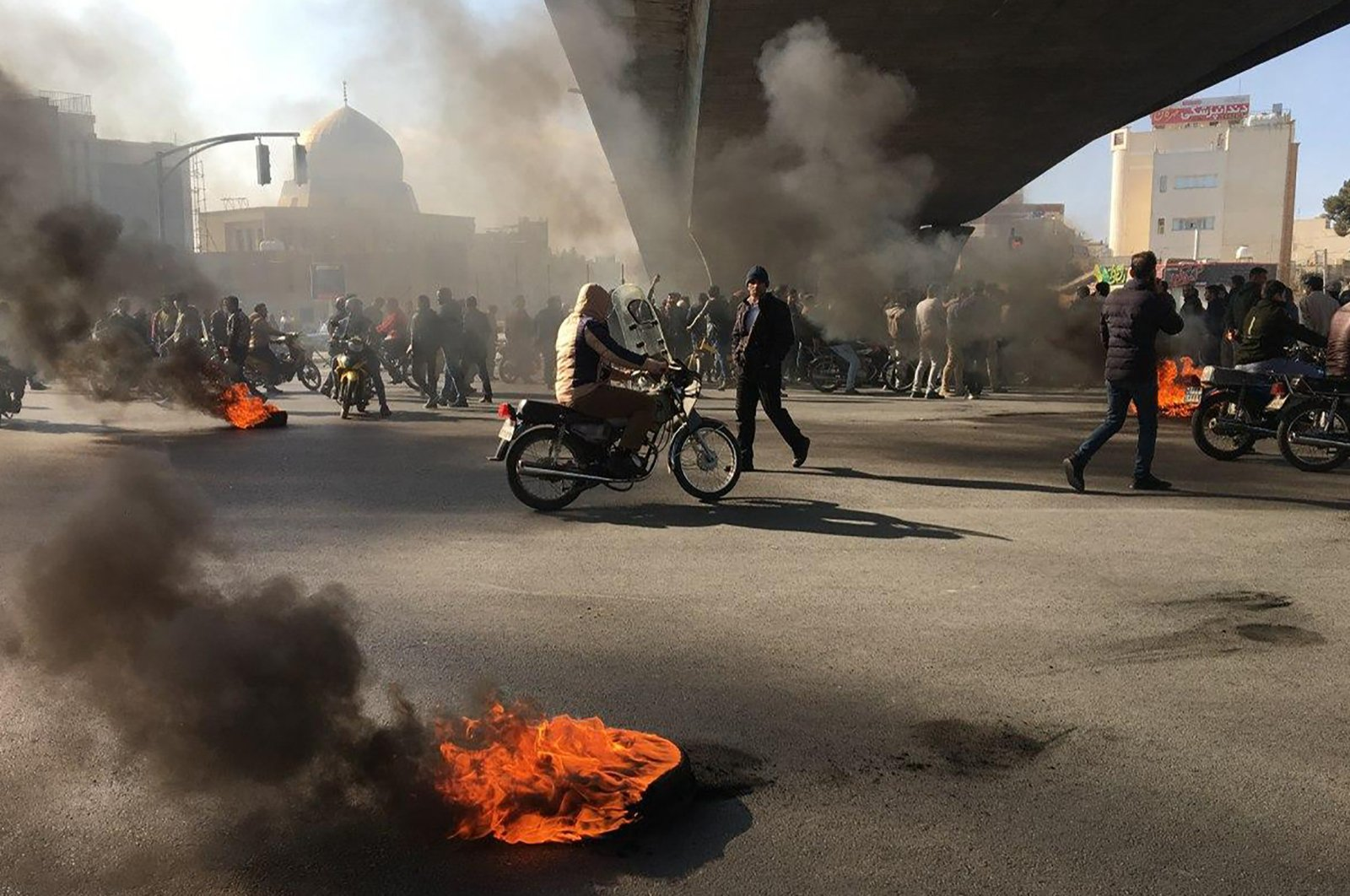 Iranian protesters rally amid burning tires during a demonstration against an increase in gasoline prices in the central city of Isfahan, Iran, Nov. 16, 2019. (AFP Photo)