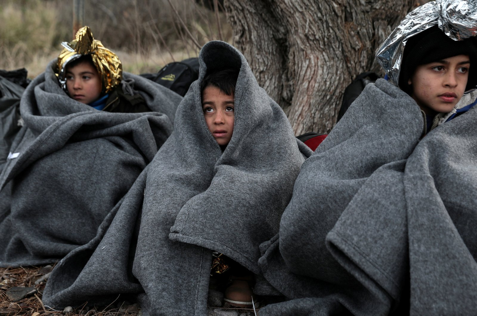 Children are covered with blankets and thermal blankets after migrants from Afghanistan arrived on a dinghy on a beach near the village of Skala Sikamias on the island of Lesbos, Greece, Feb. 28, 2020. (REUTERS Photo)