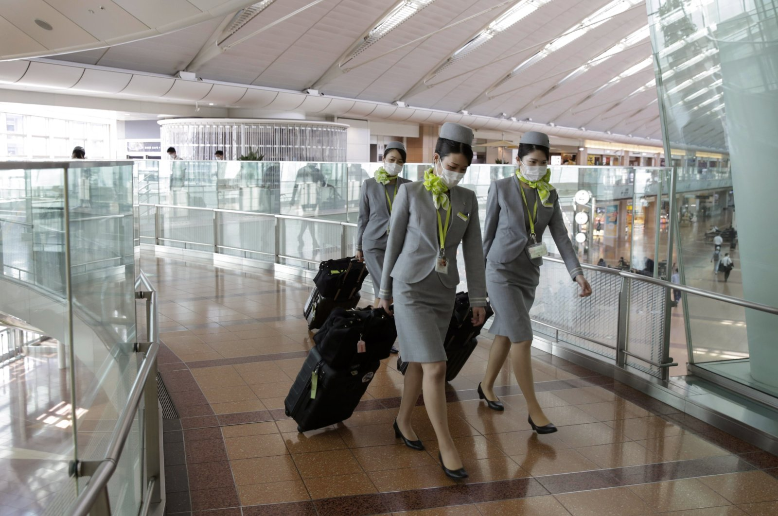 Flight attendants wearing protective masks walk toward a crew entrance at Haneda Airport in Tokyo, Japan, April 26, 2020. (EPA Photo)