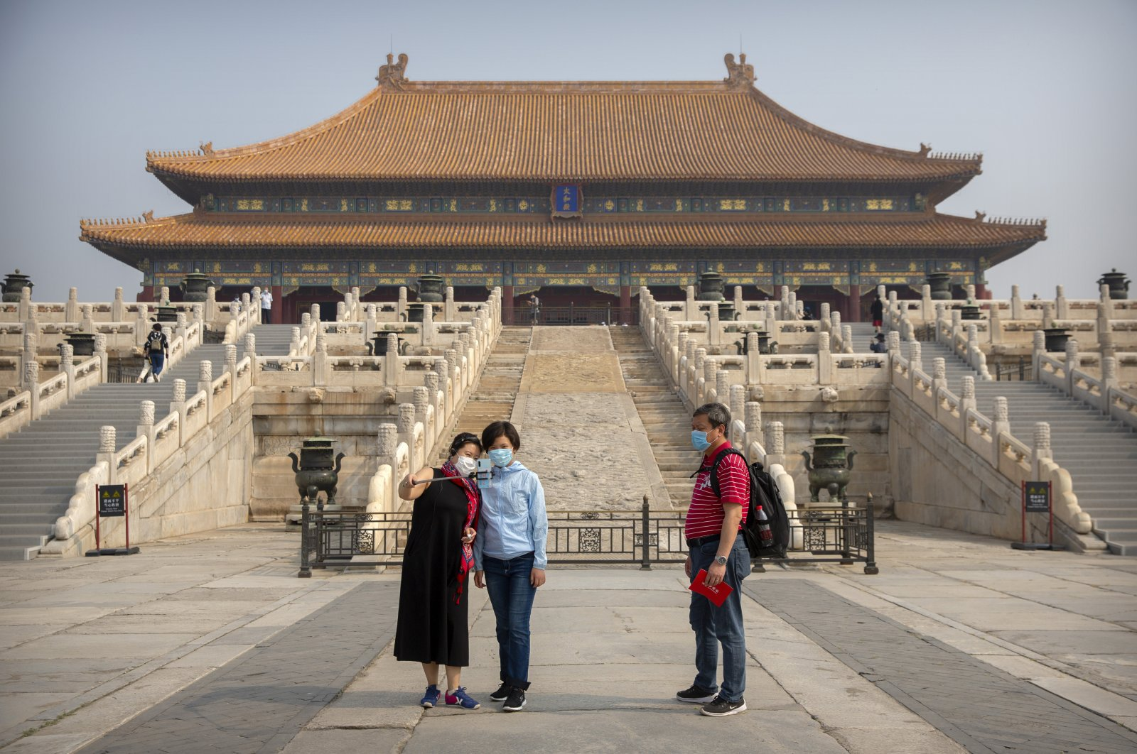Visitors wearing face masks to protect against the new coronavirus pose for a selfie in the Forbidden City in Beijing, May 1, 2020. (AP Photo)