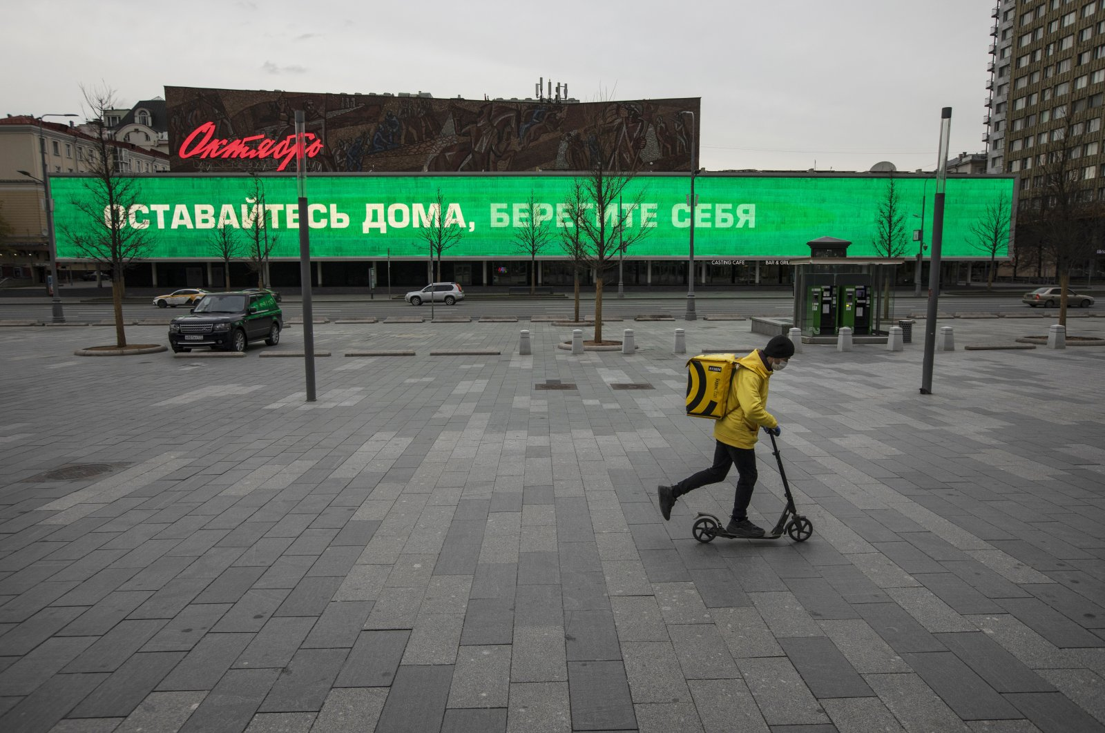 "A food delivery courier rides a scooter in the empty New Arbat Avenue, past a sign that reads, ""Stay home, take care of yourself,"" displayed on the October movie theater, Moscow, April 30, 2020. (AP Photo)"