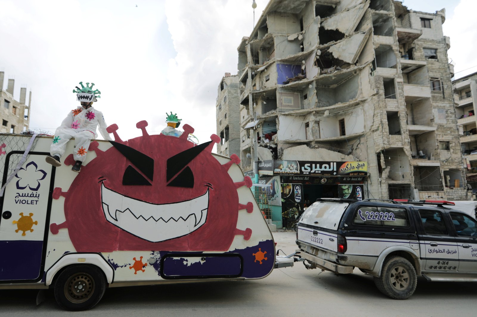 Volunteers dressed in coronavirus-themed costumes stand on a vehicle during a campaign organised by the Violet Organization, in an effort to spread awareness and encourage safety amid coronavirus disease (COVID-19) fears, in the opposition-held Idlib city, Syria, April 29, 2020. (REUTERS Photo)