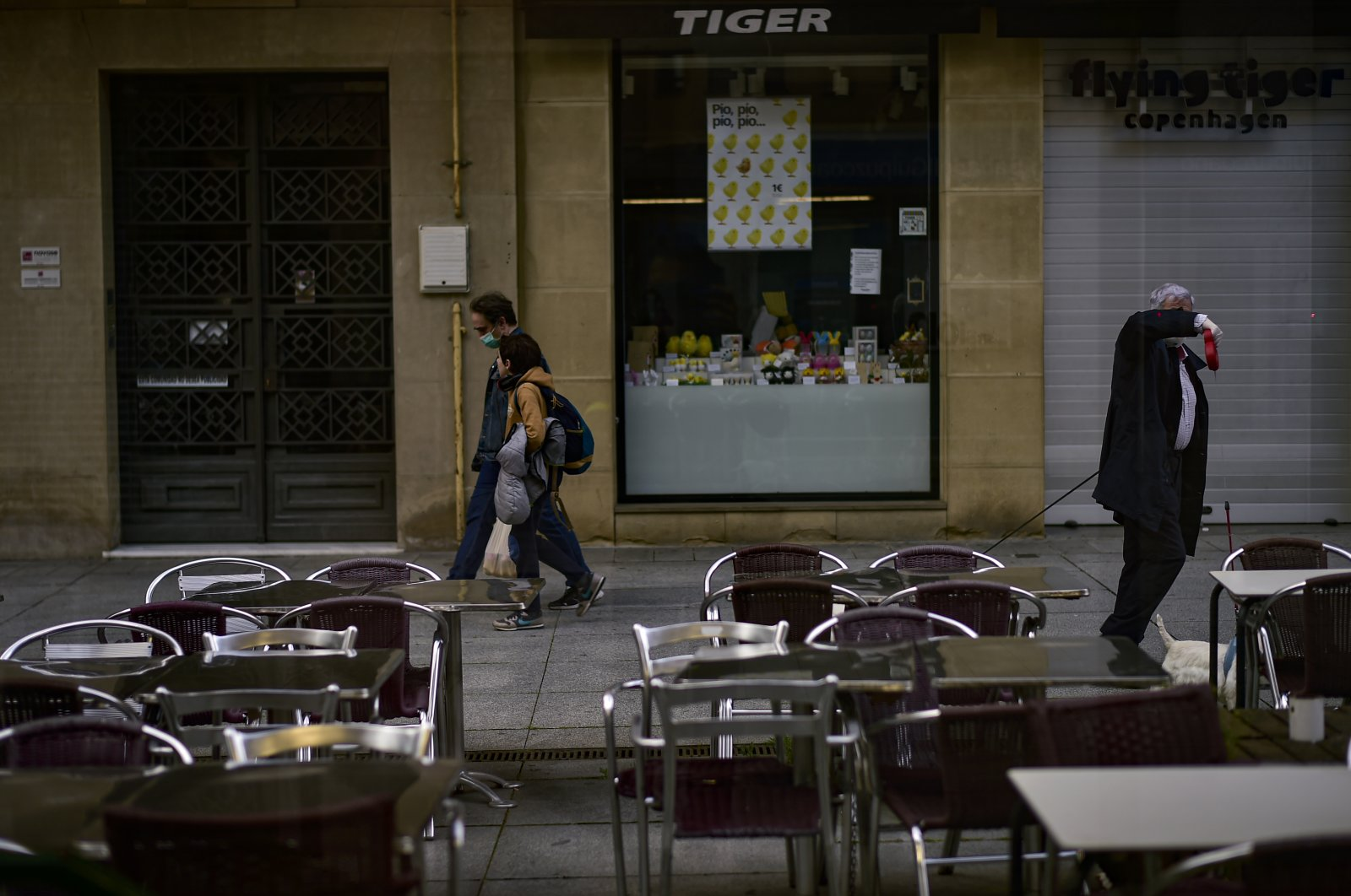 A man covers his face while walking past an empty bar in Pamplona, Spain, April 30, 2020. (AP Photo)