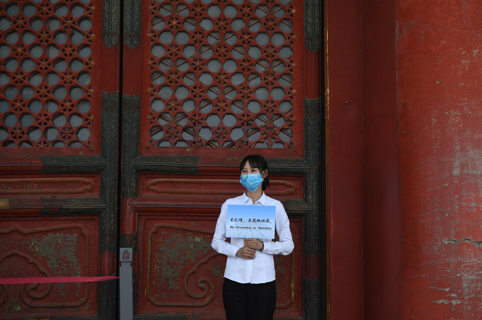 """An staff member wears a face mask as a preventive measure against the COVID-19 coronavirus as she holds a """"No crowding or spitting"""" sign in the Forbidden City, the former palace of China's emperors, in Beijing on May 1, 2020. (AFP Photo)"""