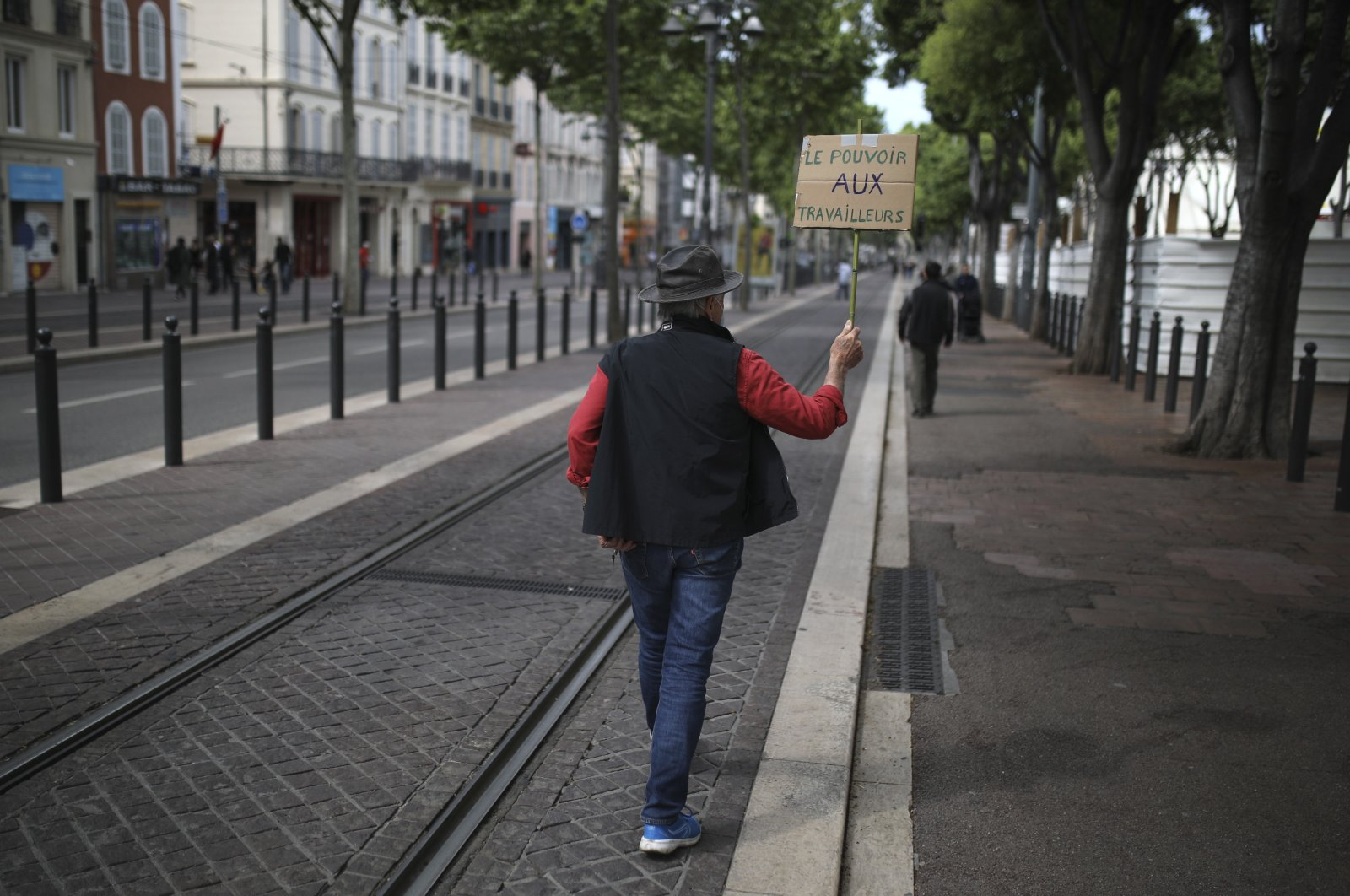 """A lonely protester holds a poster reading """"Power to workers,"""" Marseille, May 1, 2020. (AP Photo)"""