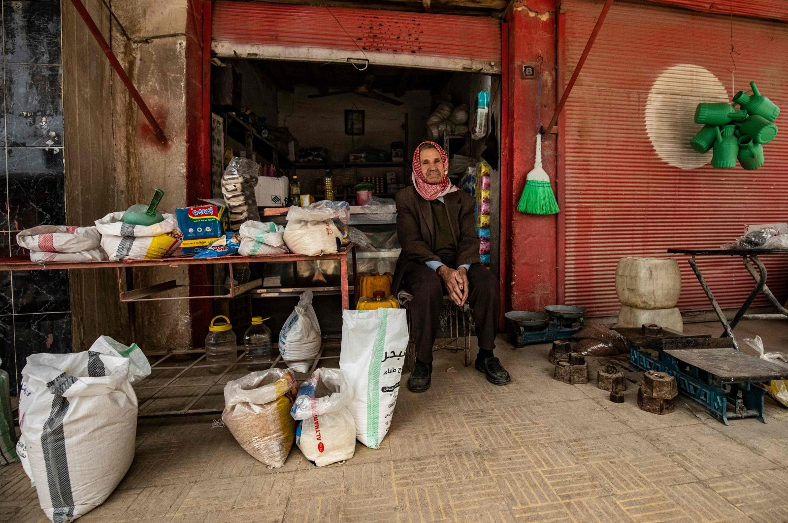 A Syrian man sits outside his store in the city of Qamishli in Syria's northeastern Hasakeh province, April 24, 2020. (AFP)