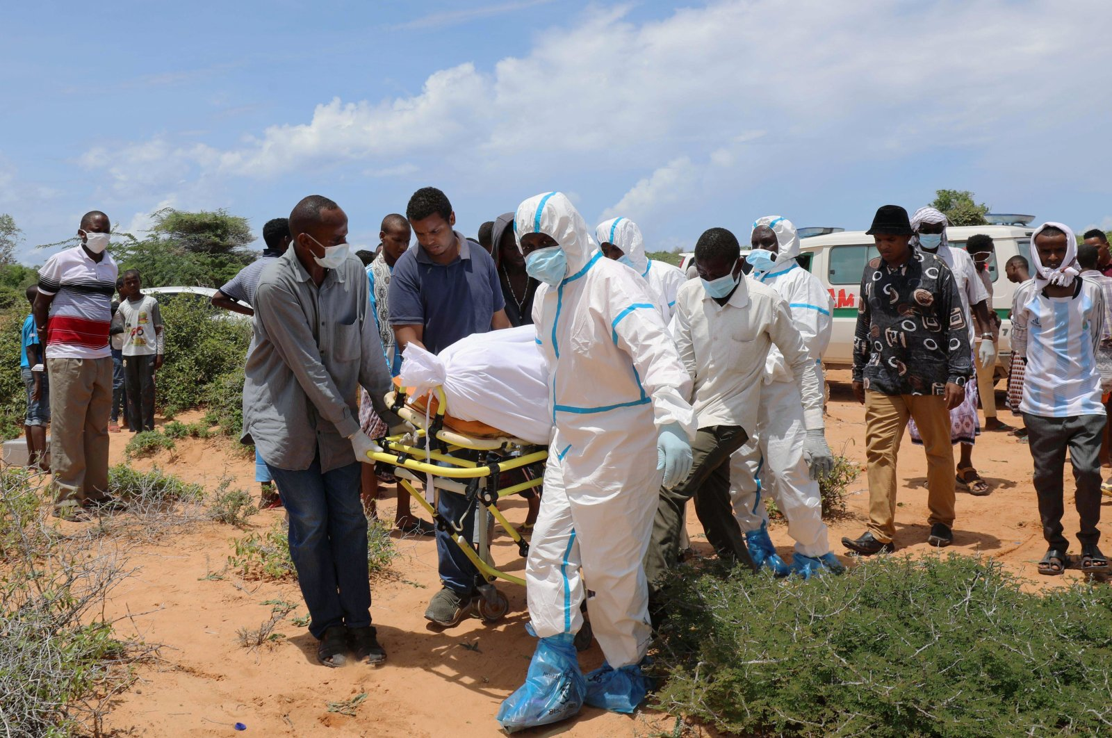 Somali workers in protective suits and civilians carry the body of a man suspected to have died of the coronavirus disease, for burial in Madina district outside of Mogadishu, Somalia April 30, 2020. REUTERS