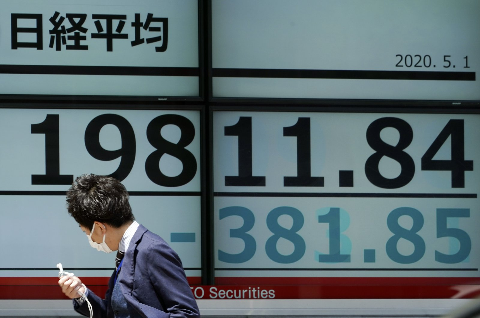 A man walks past an electronic stock board showing Japan's Nikkei 225 index at a securities firm in Tokyo Friday, May 1, 2020.(AP Photo)